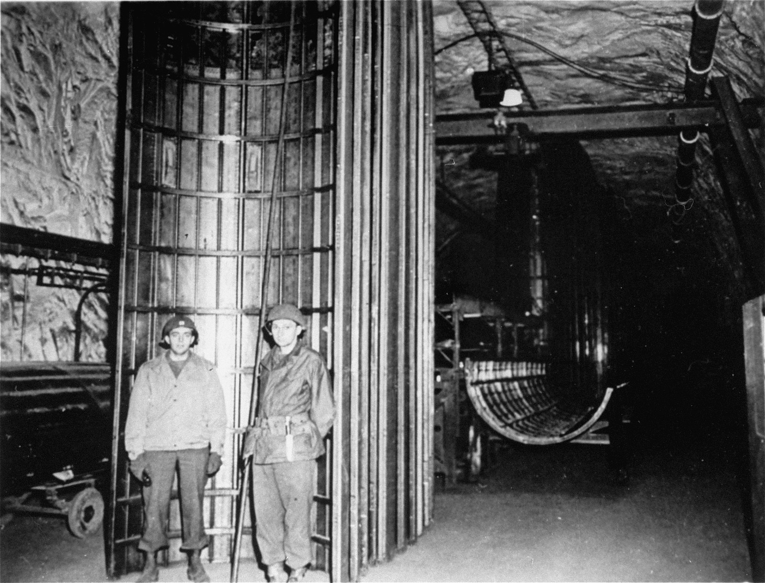 Two American soldiers stand next to a completed half-section of a V-2 fuselage in the underground rocket factory at Dora-Mittelbau.