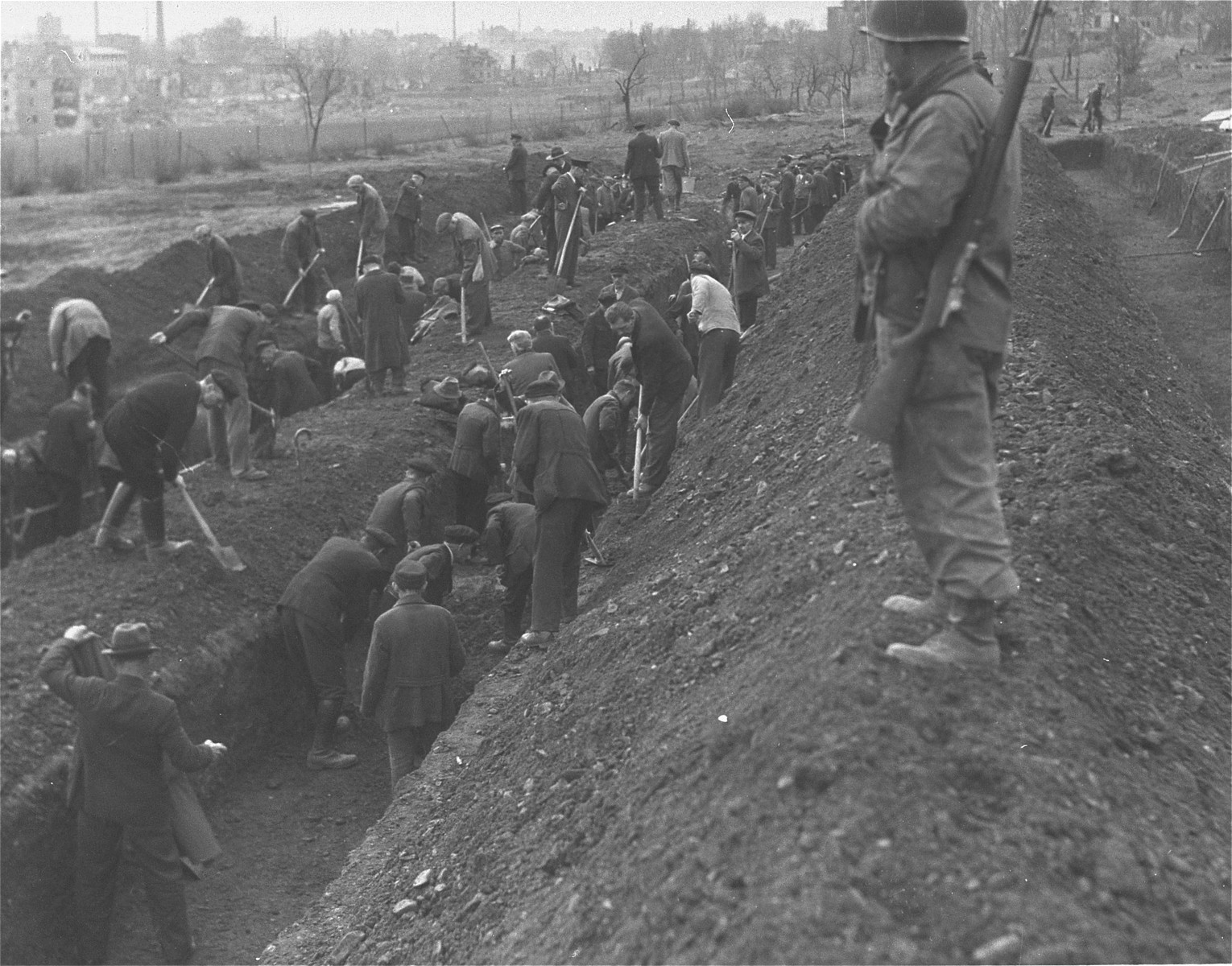 "German civilians from the town of Nordhausen dig mass graves for the victims of the Nordhausen concentration camp.  The original Signal Corps caption reads, ""U.S. TROOPS OVERRUN NAZI SLAUGHTER HOUSE.  The bodies of hundreds of former slave workers of the Nazis were discovered by soldiers of the Third Armored and 104th Infantry Divisions First U.S. Army, in ""Lager-Nordhausen,"" Nazi concentration camp in Nordhausen, Germany, which usually contained between 3,000 and 4,000 prisoners. The dead lay beside the sick and dying and the Nazi camp masters made no attempt to check the contagious diseases and gangrene suffered by maltreated prisoners of many nationalities.  The bodies, which were no more than skeletons, were buried by German civilians who were also forced to dig mass graves.  The few prisoners still alive, who had been beaten, maltreated in other ways and starved by the Nazis, have been removed to allied hospitals.  Troops of the First U.S. Army entered Nordhausen April 10, 1945.  The Reich city, 120 miles southwest of Berlin, was a manufacturing center for Nazi V-weapons.   BIPPA                                                         EA 62445  THIS PHOTO SHOWS: Guarded by a soldier of the First U.S. Army, civilians of Nordhausen, Germany, dig mass graves for the bodies of the camp inmates. U.S. Signal Corps Photo ETO-HQ-45-32273 SERVICED BY LONDON OWI TO LIST B CERTIFIED AS PASED BY SHAEF CENSOR"