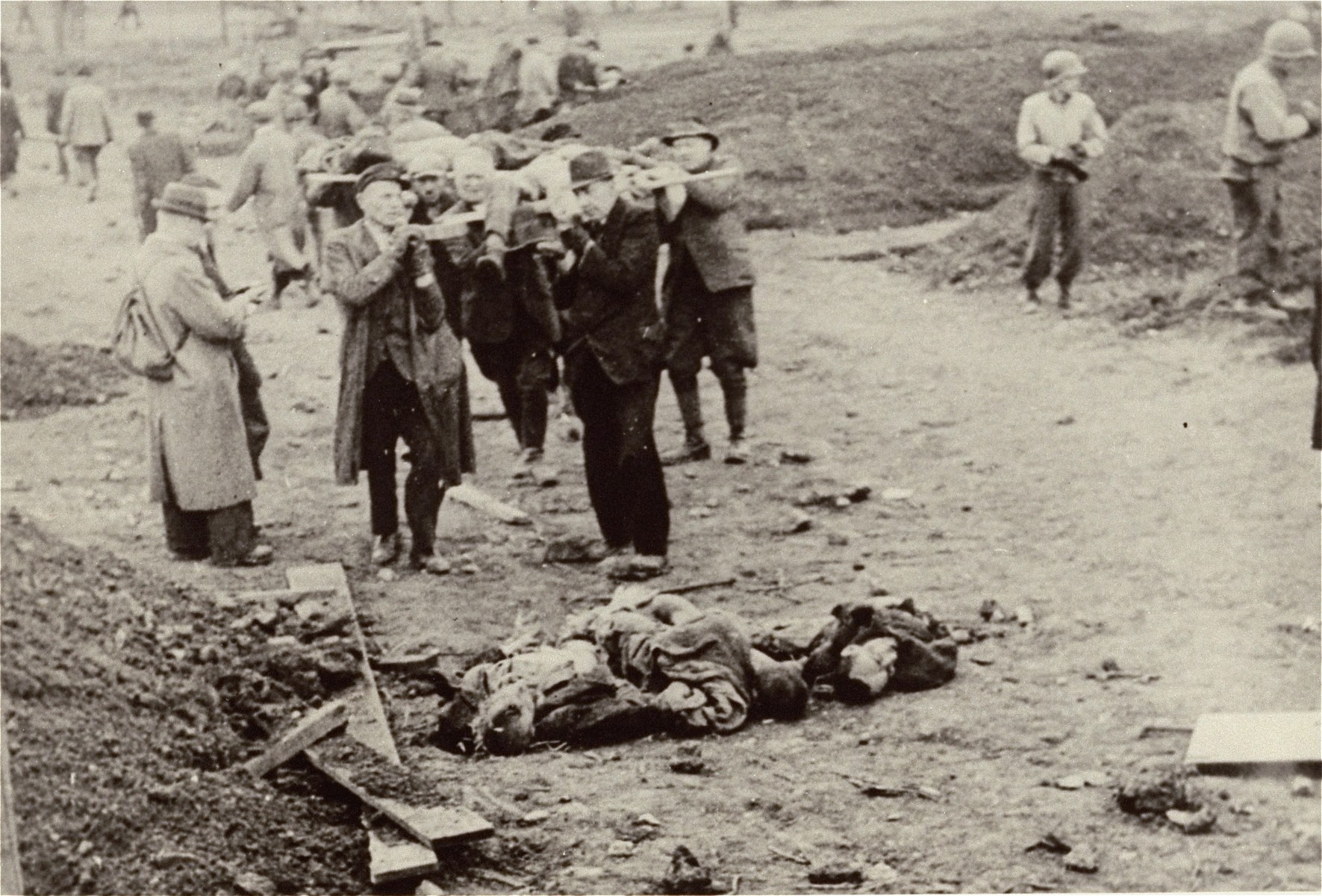 German civilians from the town of Nordhausen bring corpses to mass graves for burial.
