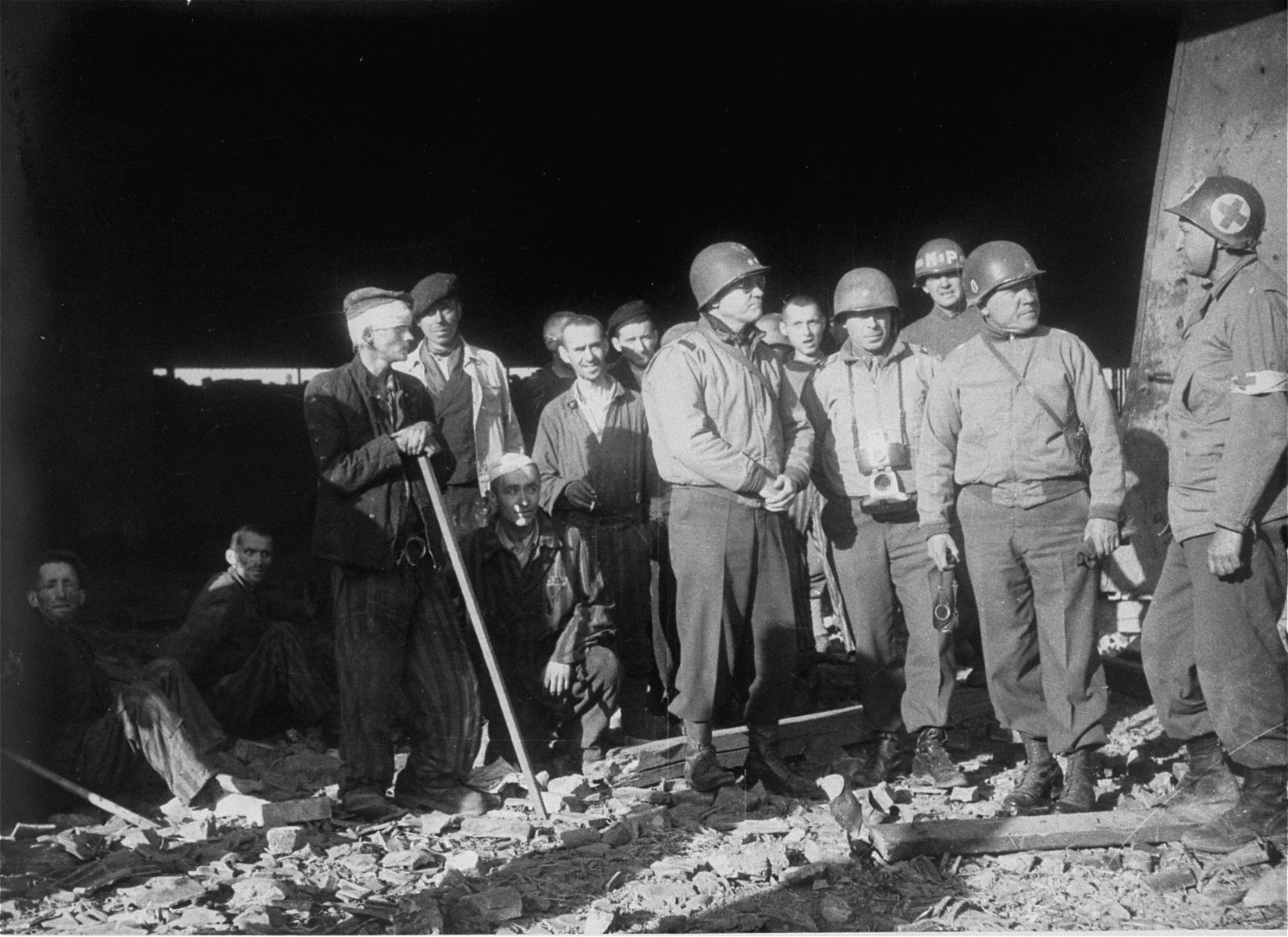 American officers speak with a medical officer while on an inspection of the ruins of the Boelke Kaserne in the Nordhausen concentration camp.    The man speaking with the corpsman is Major General J. Lawton Collins.  To his right are Brigadier General Truman E. Boudinot and Brigadier General Doyle O. Hickey.