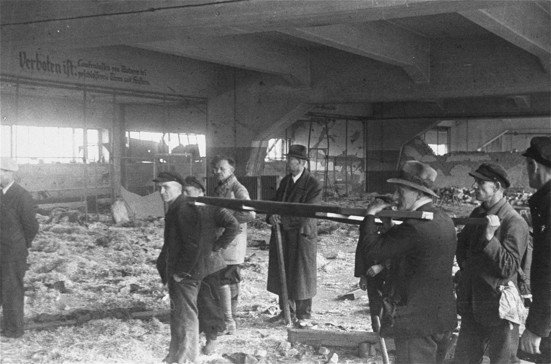 German civilians from the town of Nordhausen remove corpses from the central barracks (Boelke Kaserne) in the Nordhausen concentration camp.