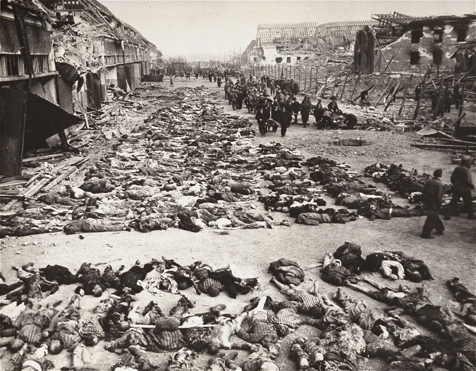 German civilians remove the bodies of prisoners killed in the Nordhausen concentration camp and lay them out in long rows outside the central barracks (Boelke Kaserne).
