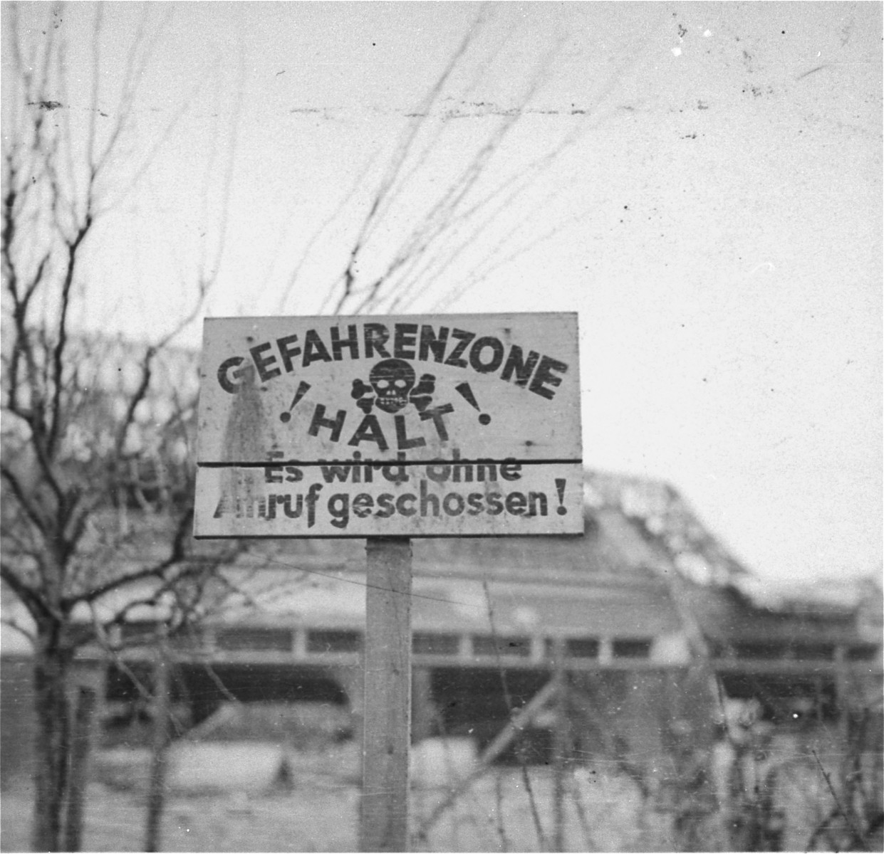 """View of a sign on the perimeter of the compound in the Nordhausen concentration camp warning that persons who enter the """"Danger Zone"""" will be shot without warning."""