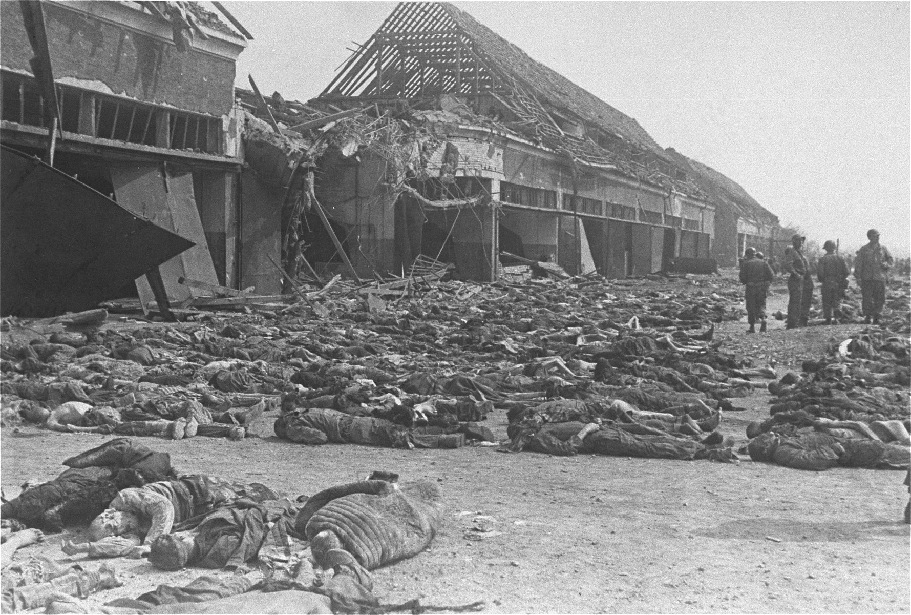 American soldiers stand among hundreds of corpses laid out in rows outside the central barracks (Boelke Kaserne) in the Nordhausen concentration camp.