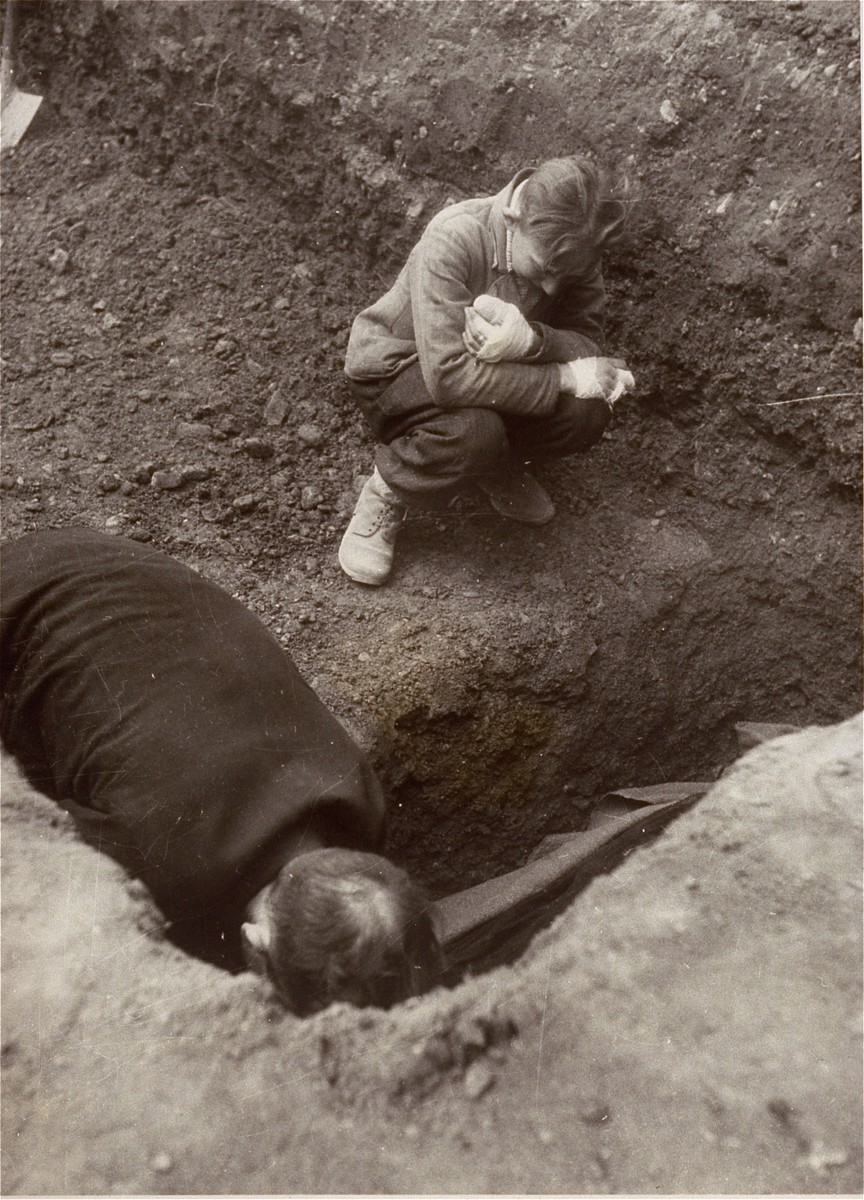 A Polish boy, Michael Kallaur, weeps while helping his father bury the body of his grandmother, Elizabeth Kallaur, who died in the Nordhausen concentration camp.   Elizabeth's head had been severed shortly before liberation.  The Kallaur family was sent to Nordhausen as punishment for helping Jews in the Pinsk region.  These survivors would not allow the Germans to touch their dead, even after Colonel D.B. Hardin ordered the civilian population of the town of Nordhausen to bury the corpses of prisoners found in the Nordhausen concentration camp.