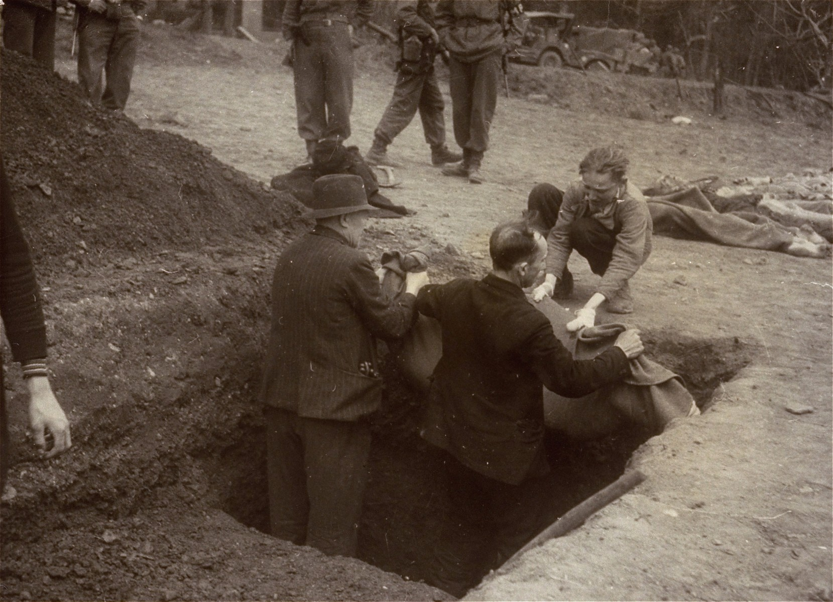 A Polish man, Walter Kallaur and his son, Michael, bury the boy's grandmother, Elizabeth Kallaur who died in the Nordhausen concentration camp, as American soldiers look on.    Elizabeth's head had been severed shortly before liberation.  The Kallaur family was sent to Nordhausen as punishment for helping Jews in the Pinsk region.  These survivors would not allow the Germans to touch their dead, even after Colonel D.B. Hardin ordered the civilian population of the town of Nordhausen to bury the corpses of prisoners found in the Nordhausen concentration camp.