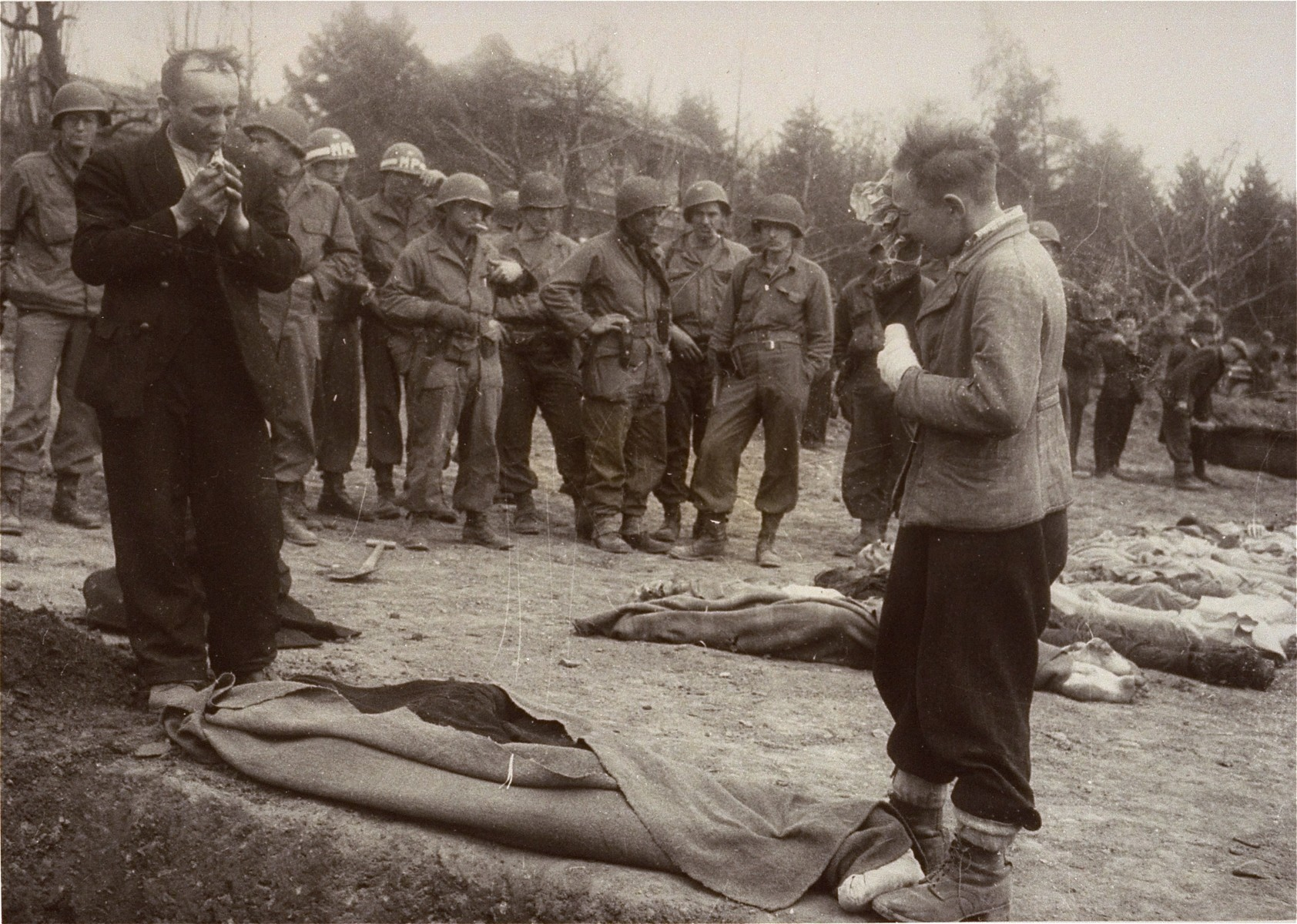 A Polish boy, Michael Kallaur, weeps while his father Walter prays over the body of the boy's grandmother, Elizabeth Kallaur,who died in the Nordhausen concentration camp.   Elizabeth's head had been severed shortly before liberation.  The Kallaur family was sent to Nordhausen as punishment for helping Jews in the Pinsk region.  These survivors would not allow the Germans to touch their dead, even after Colonel D.B. Hardin ordered the civilian population of the town of Nordhausen to bury the corpses of prisoners found in the Nordhausen concentration camp.