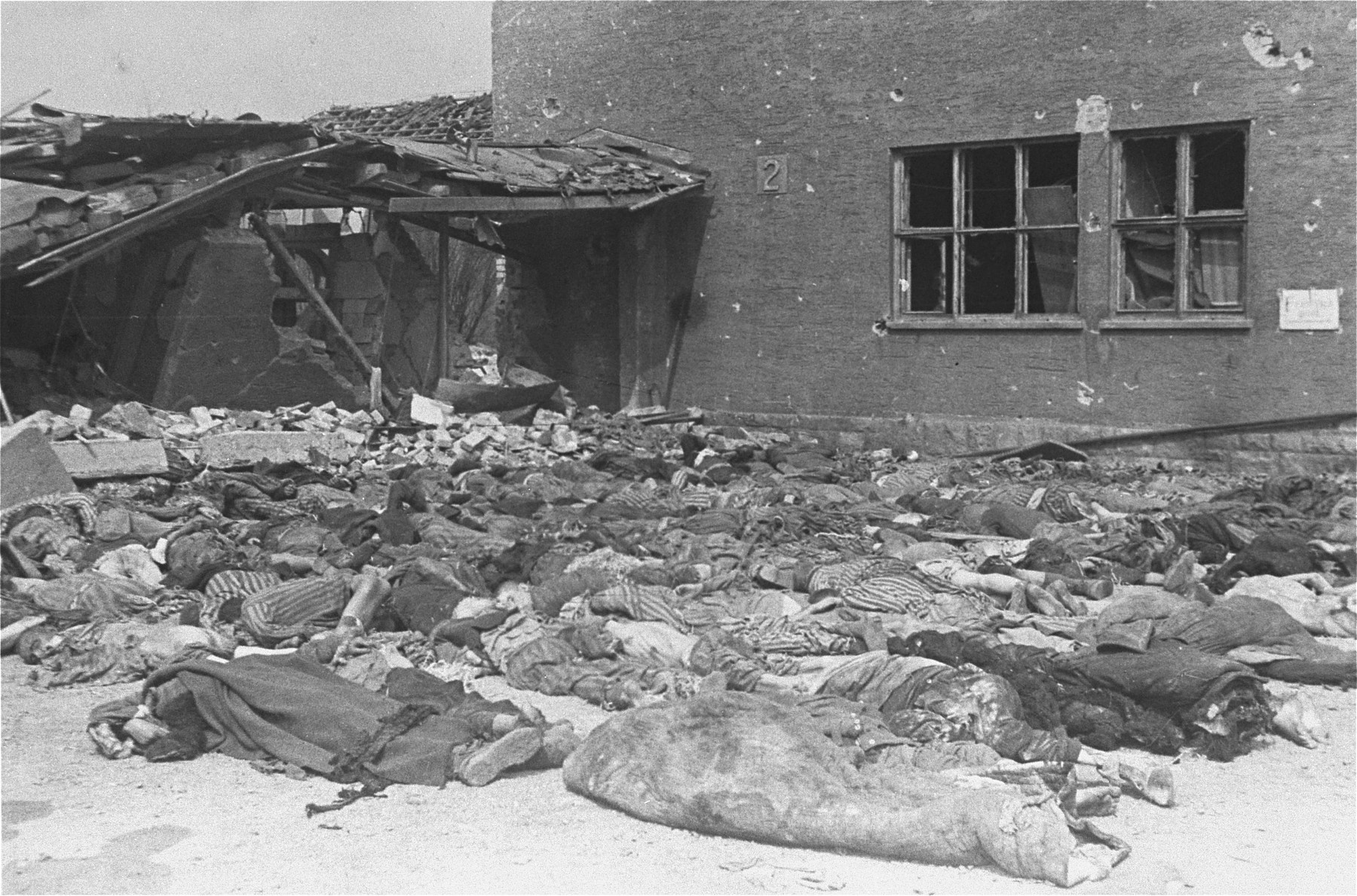 The bodies of prisoners are laid out in rows on the ground in the newly liberated Nordhausen concentration camp.