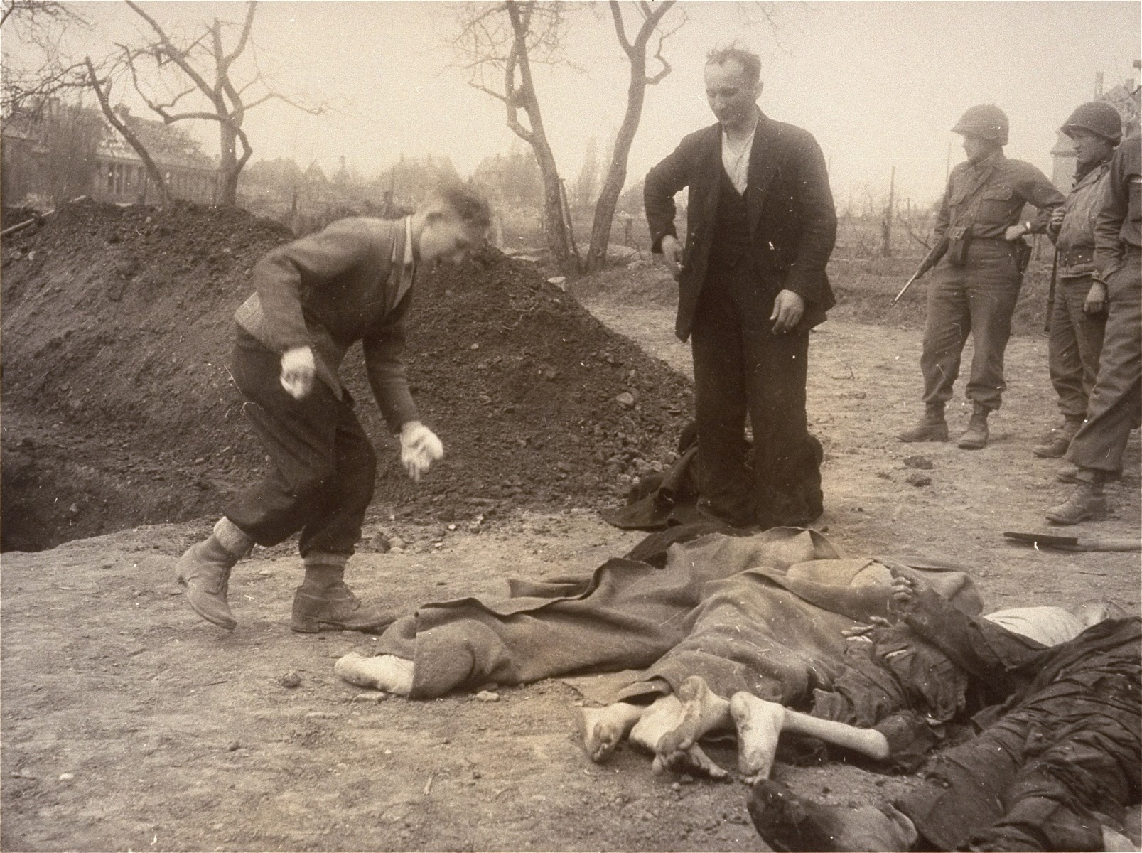 A Polish boy and his father bury the body of the boy's grandmother, who died in the Nordhausen concentration camp.   The young boy on left is Michael Kallaur (about 14 years old) who found the body of his grandmother,  Elizabeth Kallaur, with her head severed off.  His father Walter Kallaur stands over her.  The coat next to him was given by the army photographer to cover her when she was just found.   These survivors would not allow the Germans to touch their dead, even after Colonel D.B. Hardin ordered the civilian population of the town of Nordhausen to bury the corpses of prisoners found in the Nordhausen concentration camp.