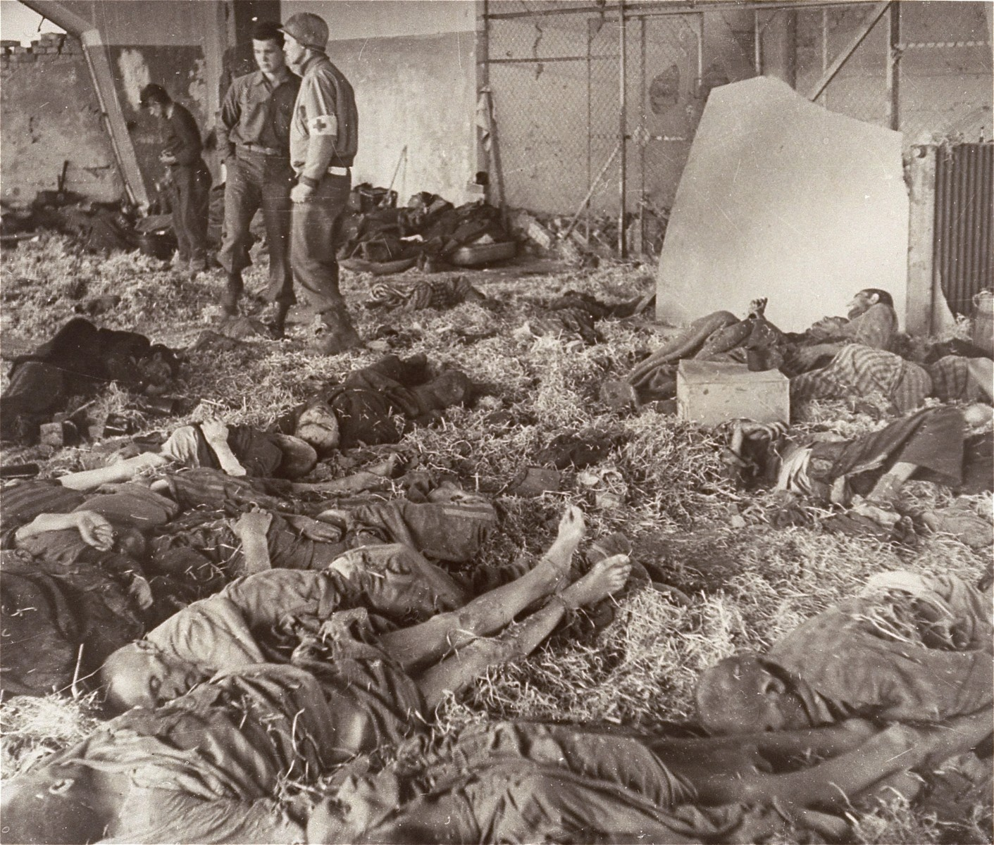 An American soldier and medical officer view the bodies of prisoners lying on the ground in a barracks in the Nordhausen concentration camp.