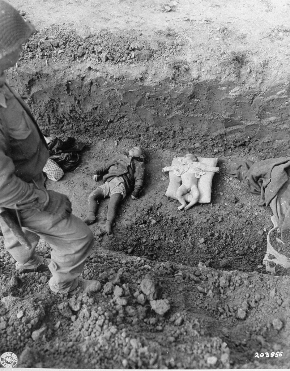"An American soldier stands above the corpses of children that are to be buried in a mass grave dug by German civilians from the nearby town of Nordhausen.  Original caption reads: ""Bodies of dead children found in concentration camp at Nordhausen lie in mass burial grave.""  Original caption from donated photograph reads:  ""The bodies of a little baby and a young child rest in a mass grave awaiting burial at the horror camp at Nordhausen, Germany.  When U.S. troops arrived in the area, they found hundreds of dead former slave workers strewn about the grounds.  Decomposing corpses lay beside the sick and dying and disease was spreading unchecked among the maltreated prisoners of many nationalities.  U.S. Army officers immediately ordered German civilians in the area to provide decent burial for the victims."""