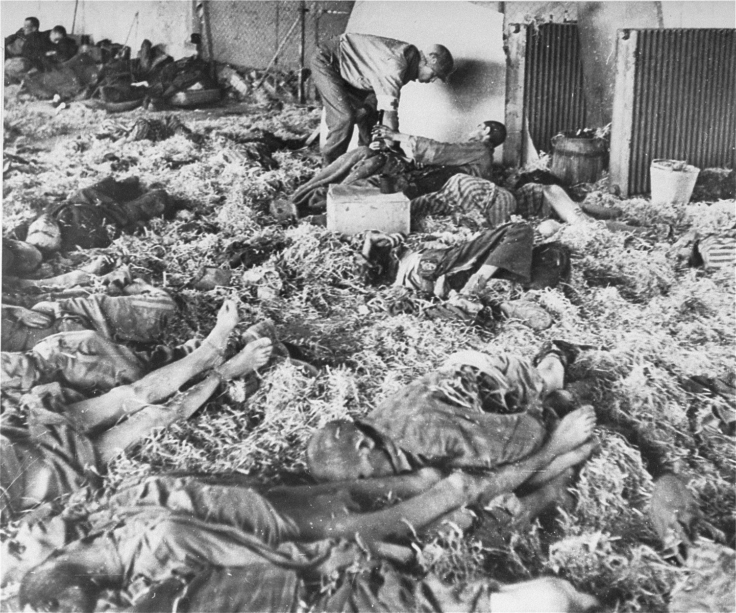 "An American medic helps a survivor who was lying amongst the corpses of dead prisoners in the ""Boelke Kaserne""."