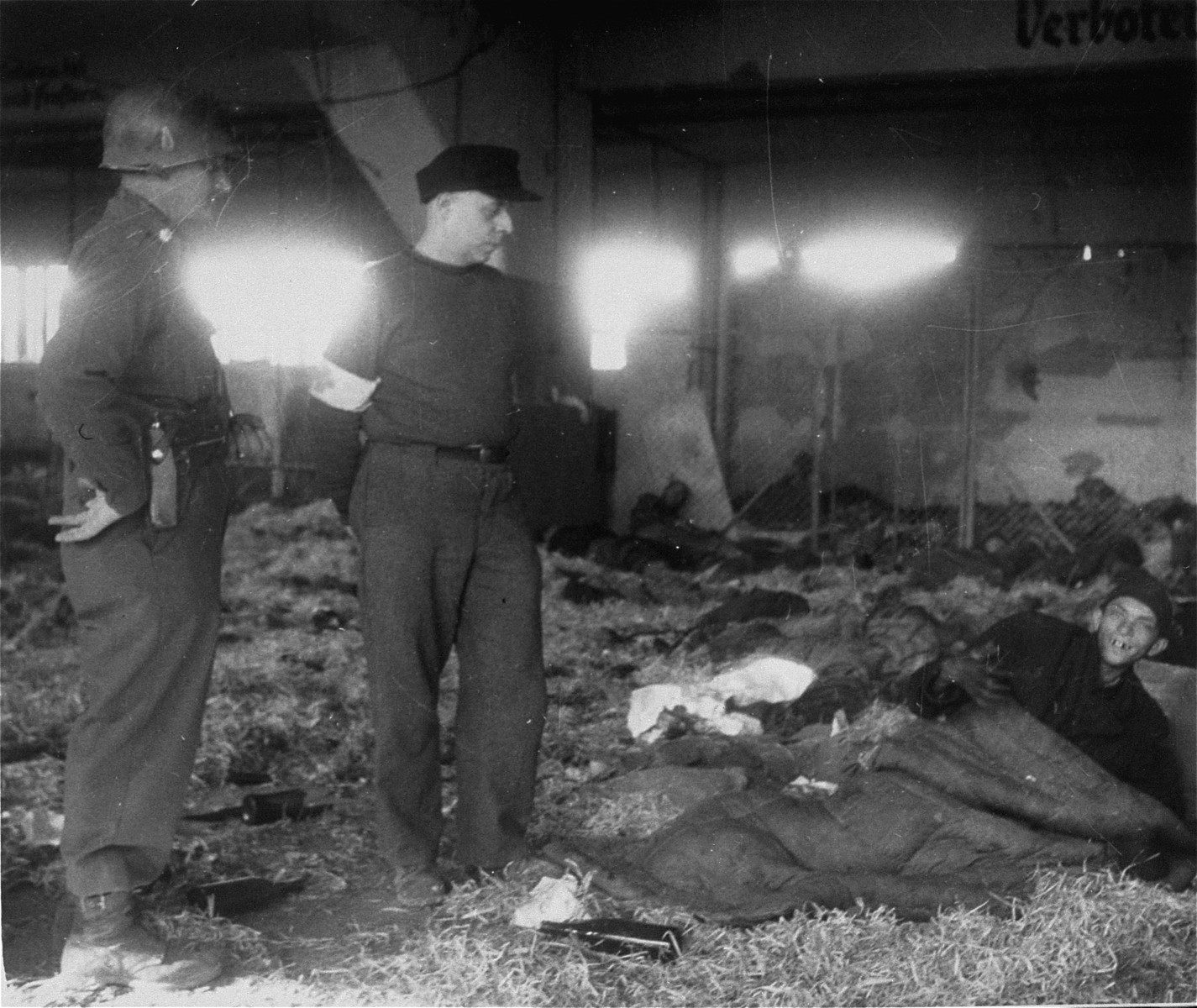 An American soldier and medical officer view the dead and the living in the barracks at the Nordhausen concentration camp.