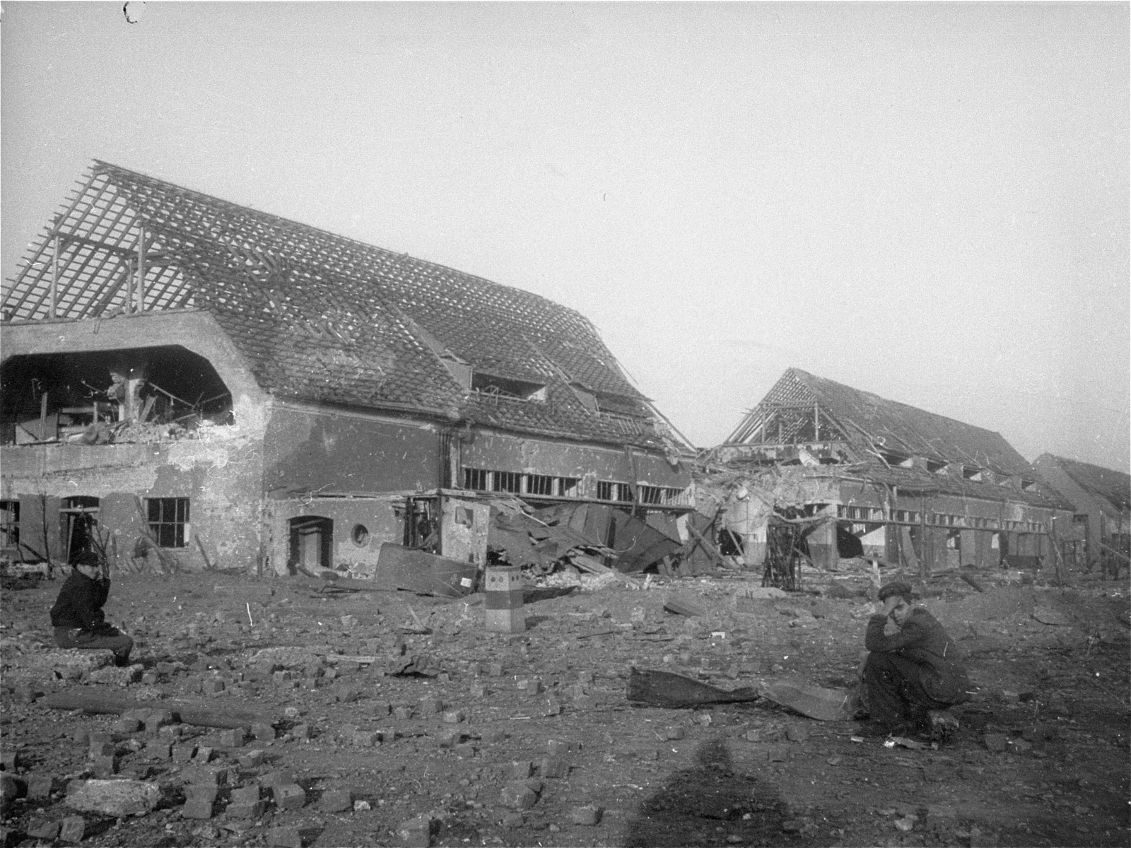 View of the ruins of the central barracks (Boelke Kaserne) in the Nordhausen concentration camp.  A survivor sits in the foreground.
