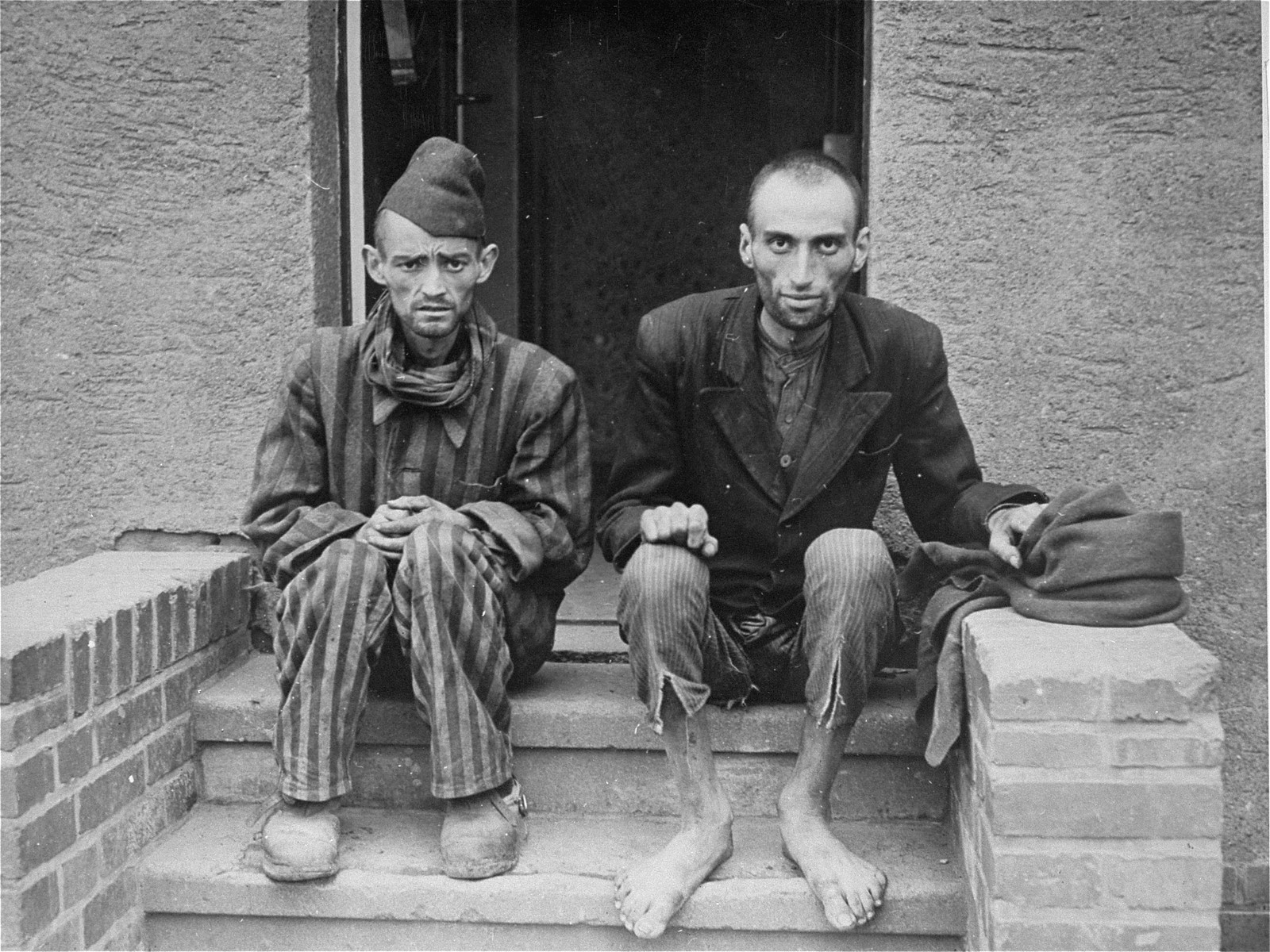 Two emaciated survivors sit outside on the stoop of a barracks in the newly liberated Nordhausen concentration camp.