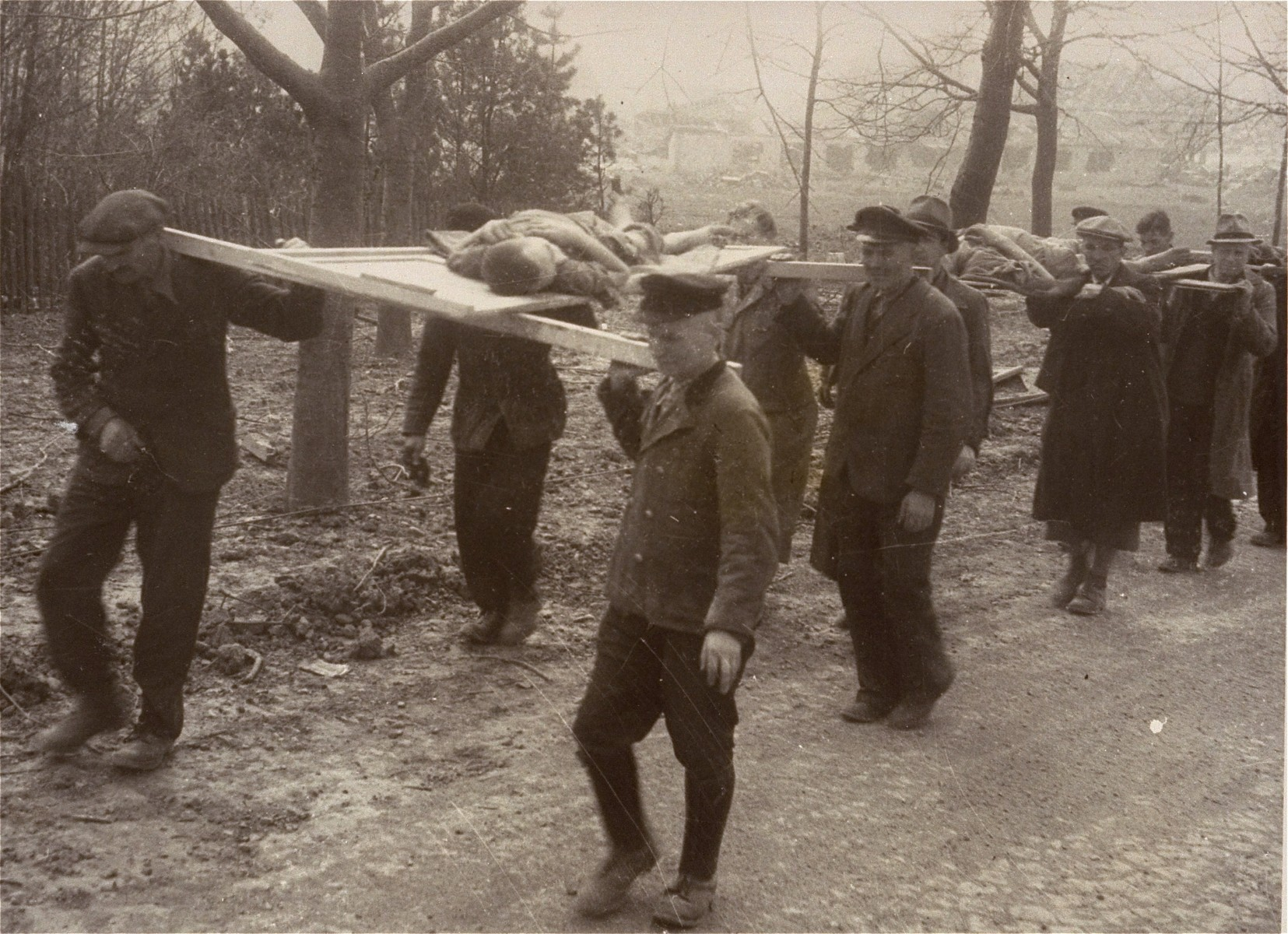 German civilians carry the corpses of prisoners from the Nordhausen concentration camp to a mass grave for burial.