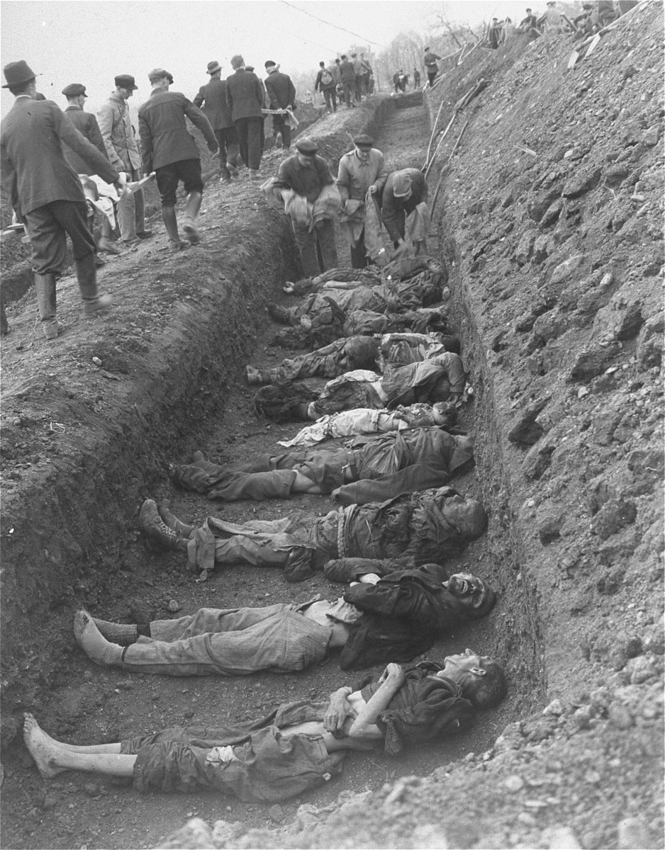 German civilians carrying corpses from the grounds of the Nordhausen concentration camp to mass graves for burial.