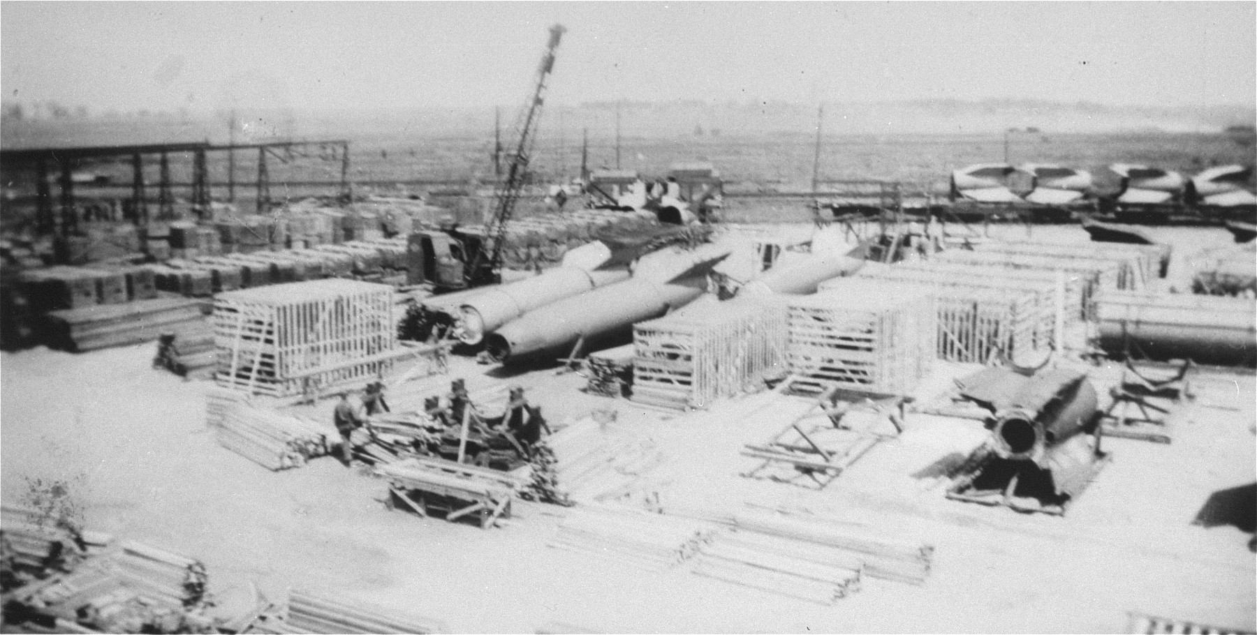 A V-2 rocket that was manufactured at Dora-Mittelbau, is being crated at the shipping docks in Antwerp for trans-shipment to the United States.  A trainload of V-2 rocket tail fins can be seen in the background.