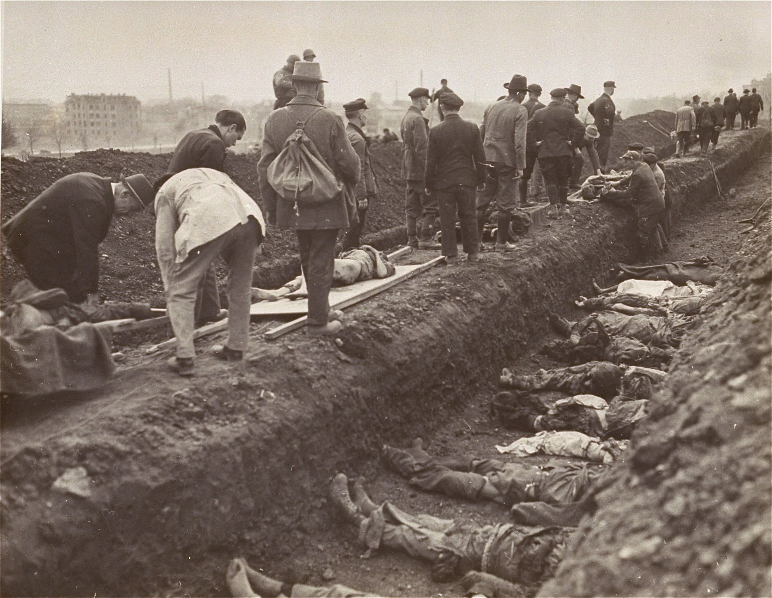"German civilians from the town of Nordhausen bury the bodies of former prisoners found in the Nordhausen concentration camp in a mass grave.  Original caption reads ""The bodies of hundreds of former slave workers of the Nazis were discovered by soldiers of the Third Army, in the ""Lager-Nordhausen"". Nazi concentration camp in Nordhausen, Germany, which usually contained between 3,000 and 4,000 prisoners.  The dead lay beside the sick and the dying and the Nazi camp masters had made no attempt to check the contagious diseases and gangrene suffered by maltreated prisoners of many nationalitites.  The bodies, which were no more than skeletons, were buried by German civilians who were also forced to dig mass graves. The few prisoners still alive, who had been beaten, maltreated in other ways and starved by the Nazis, have been removed to Allied hospitals.  Troops of the First U.S. Army entered Nordhausen, April 10, 1945.  The Reich city, 120 miles southwest of Berlin, was a manufacturing center for Nazi V-weapons""."