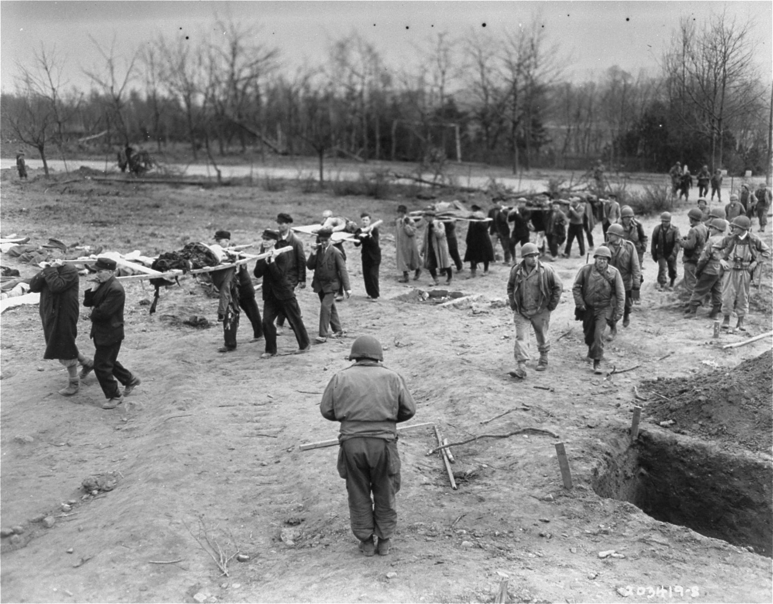 German civilians from the town of Nordhausen carry the bodies of prisoners from the Nordhausen concentration camp to mass graves.