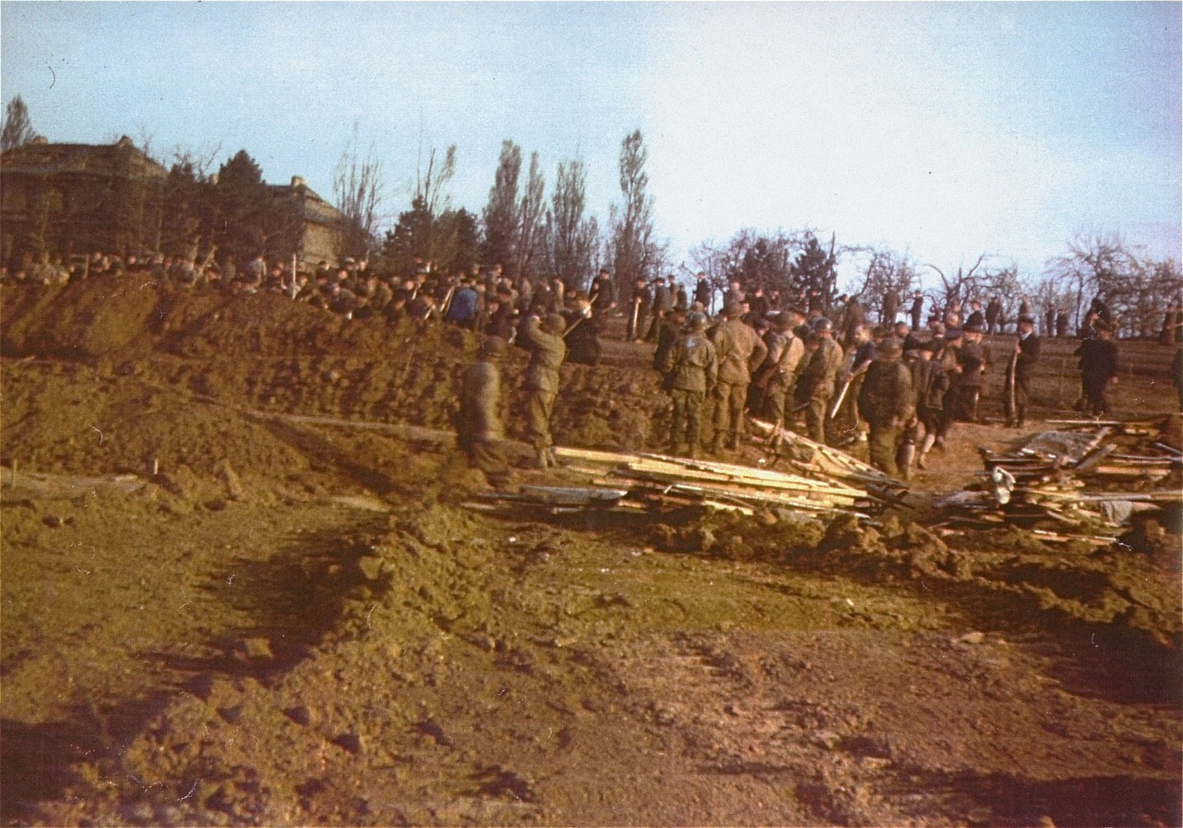 American soldiers watch as German civilians bury the corpses of prisoners found in the Nordhausen concentration camp.