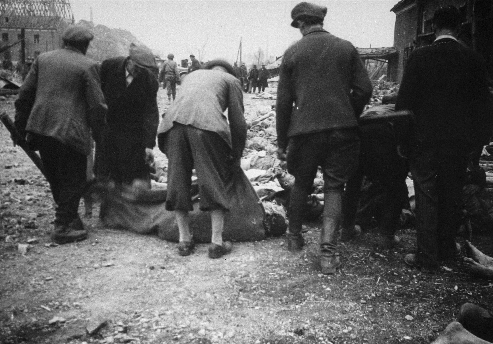 German civilians collect the corpses of prisoners killed in the Nordhausen concentration camp for burial in a mass grave.