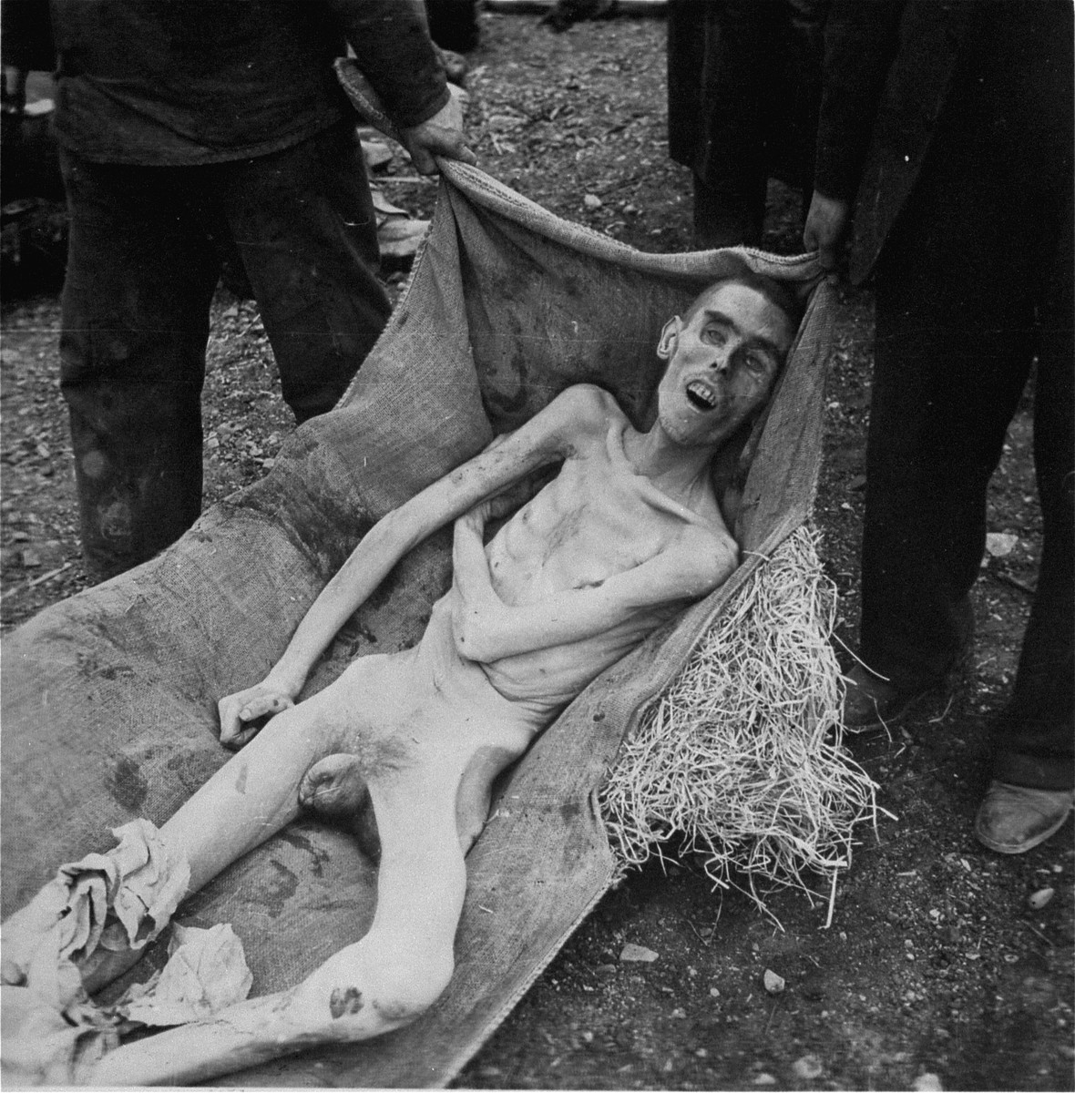 German civilians carry the corpse of a prisoner to a mass grave for burial.