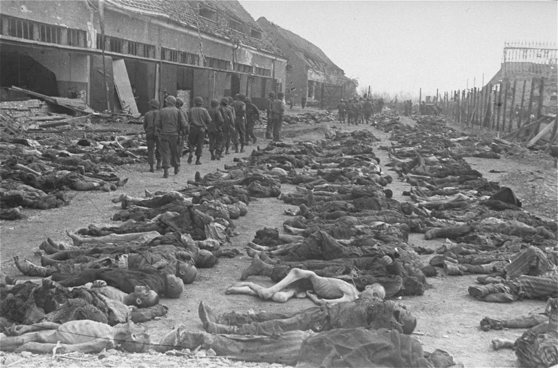 American soldiers walk past corpses that have been laid out in rows at the newly liberated Nordhausen concentration camp.