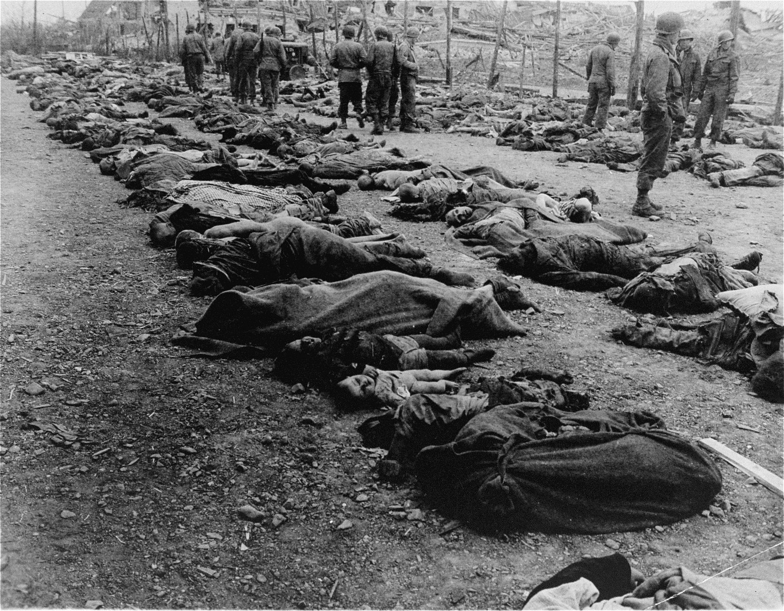 American troops stand amidst rows of corpses that were removed from the central barracks (Boelke Kaserne) of the Nordhausen concentration camp.