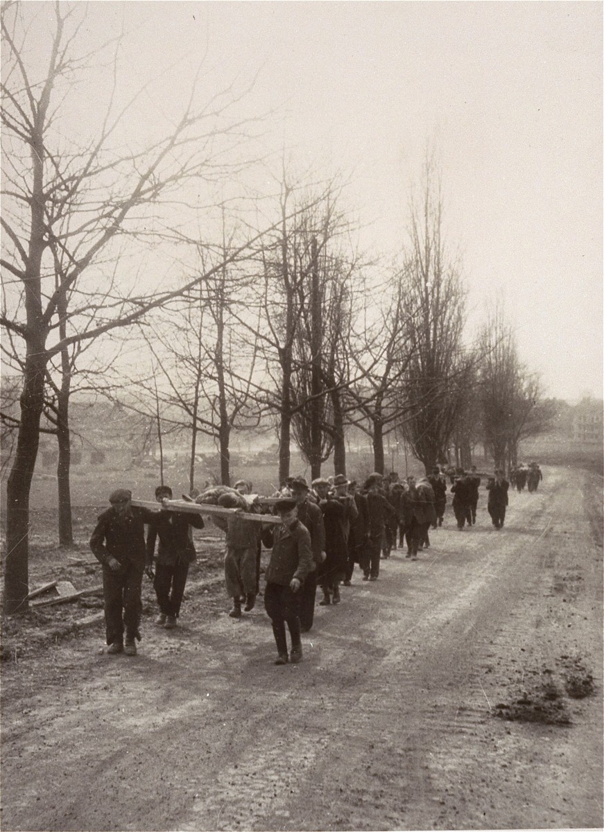German civilians from the town of Nordhausen carry the bodies of prisoners from the Nordhausen concentration camp to a mass grave for burial.