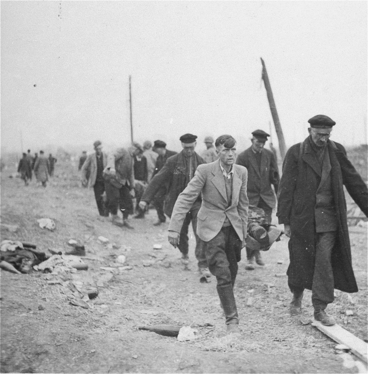 German civilians carry corpses of dead prisoners from the Nordhausen concentration camp to a mass grave for burial.
