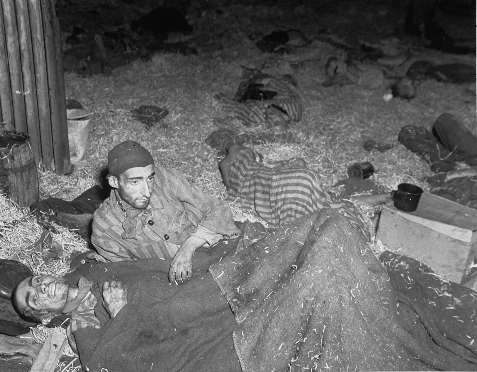 """Two survivors lie among corpses on the straw-covered floor of the barracks called the """"Boelke Kaserne."""""""