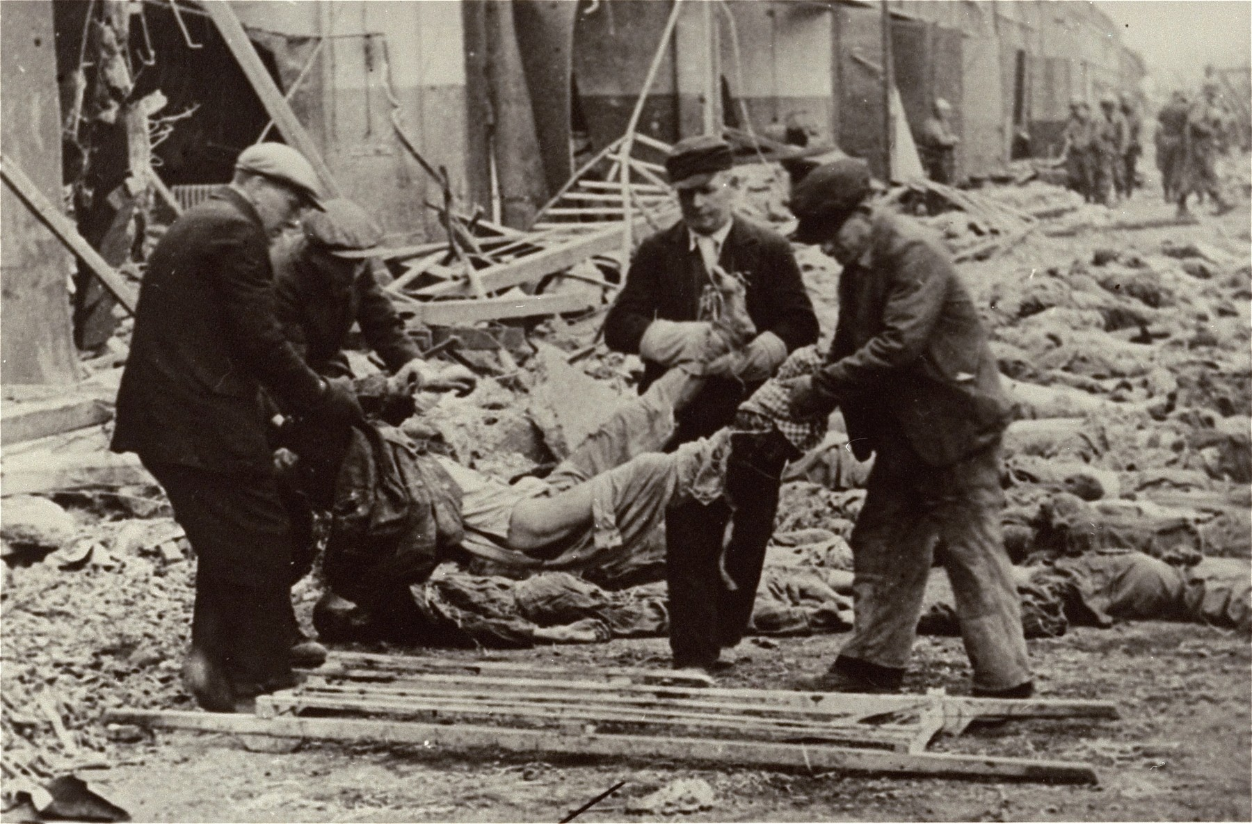 German civilians conscripted by the U.S. Army to clean the grounds of the Nordhausen concentration camp lift a corpse onto a wooden stretcher.