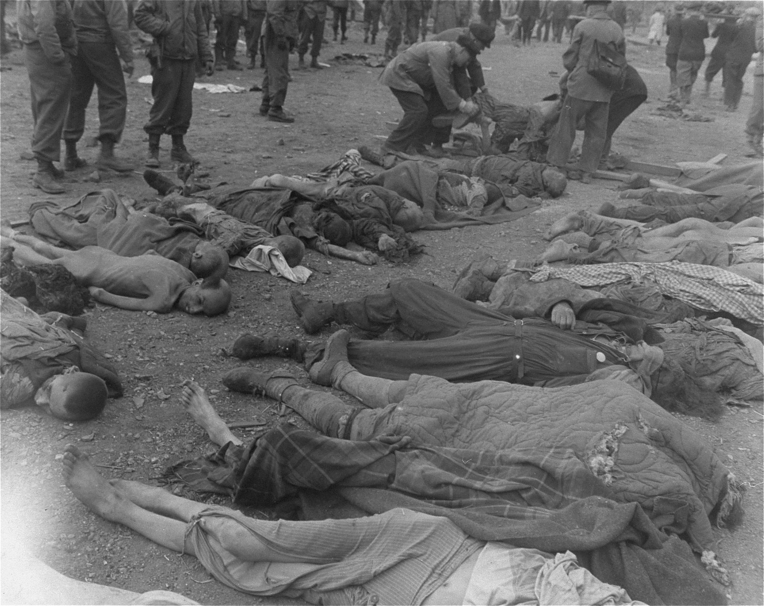German civilians remove corpses from the grounds of the Nordhausen concentration camp as American soldiers watch.