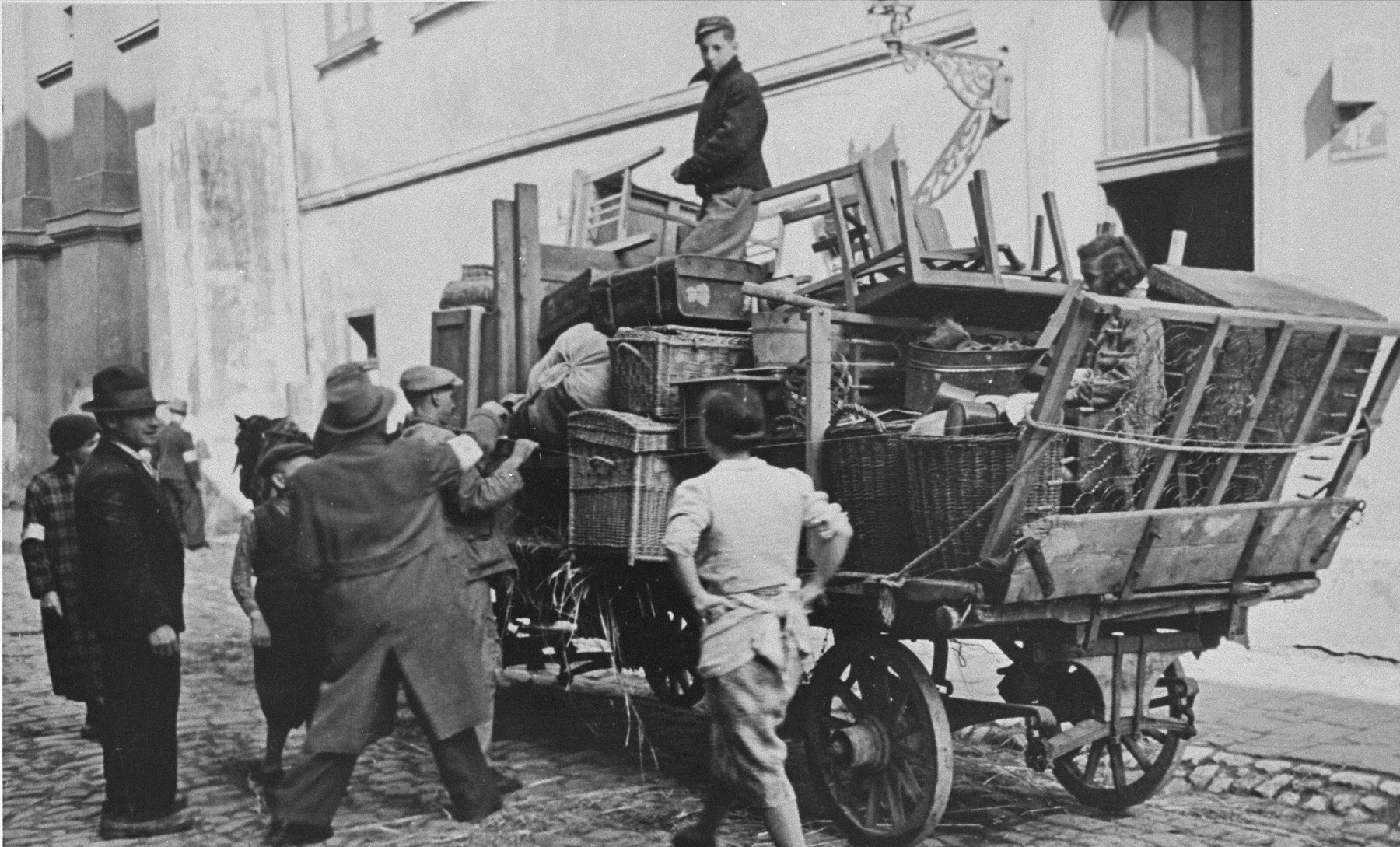 Forced to relocate to the Krakow ghetto, Jews move their belongings in horse-drawn wagons.