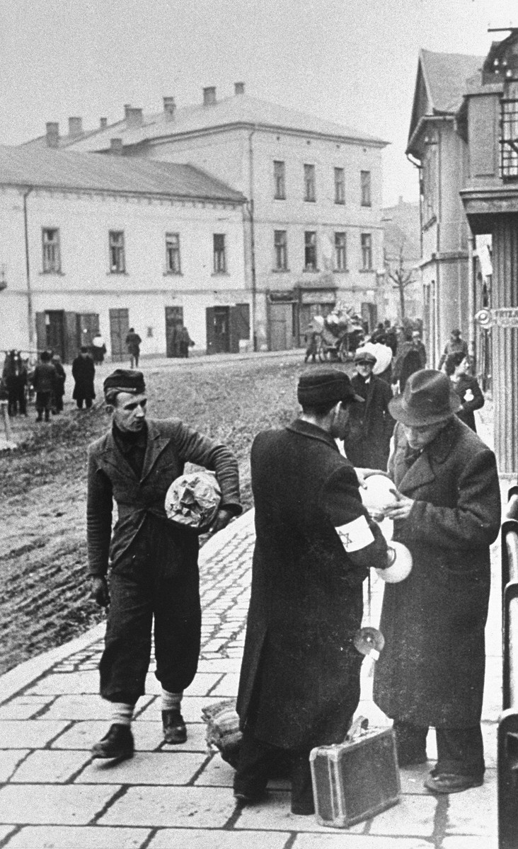 Two Jewish men examine lighting fixtures on the street in the Krakow ghetto, while a third man walks by holding a bundle under his arm.