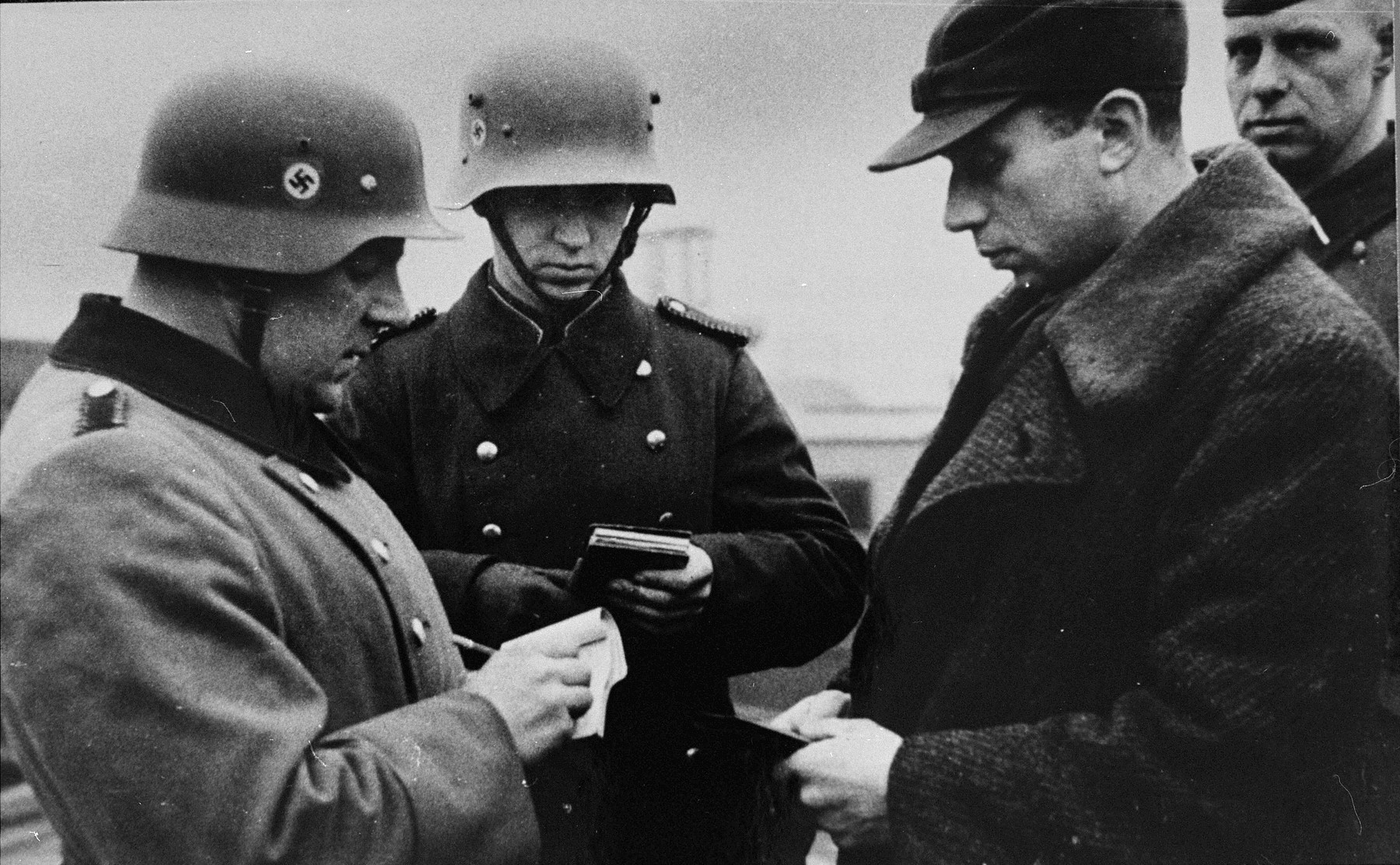 German police or soldiers check the identification papers of a Jew in the streets of Krakow.