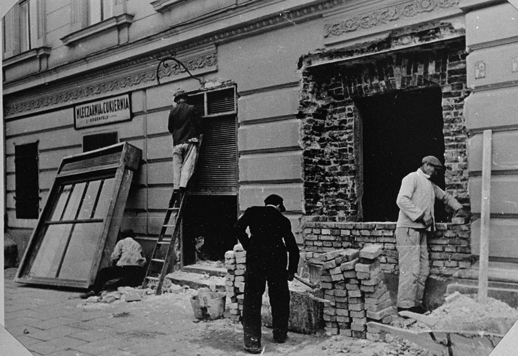 Polish laborers seal off the doors and windows of buildings on the outer periphery of the Krakow ghetto.
