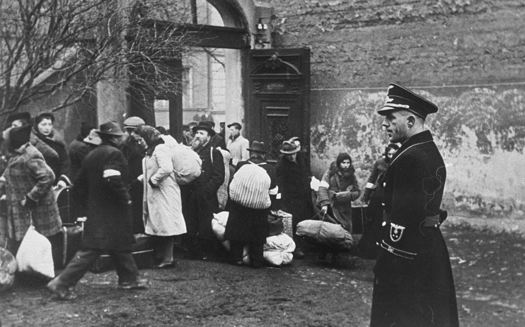 A German official supervises a deportation action in the Krakow ghetto.  Jews, assembled in a courtyard with their bundles, await further instructions.
