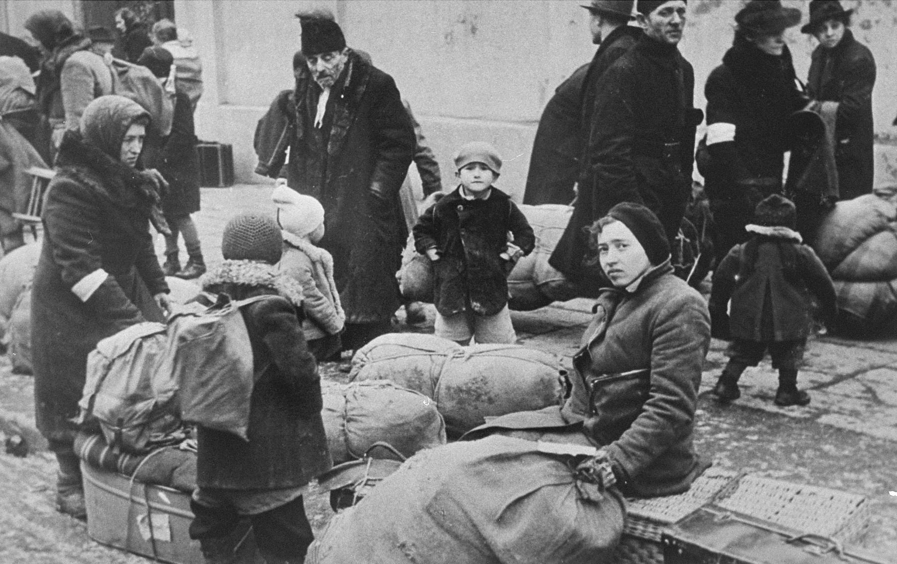 Jews assembled on the street with their bundles.  It is not clear whether they are waiting to be resettled in the Krakow ghetto, or to be taken to the trains during a deportation action in the ghetto.