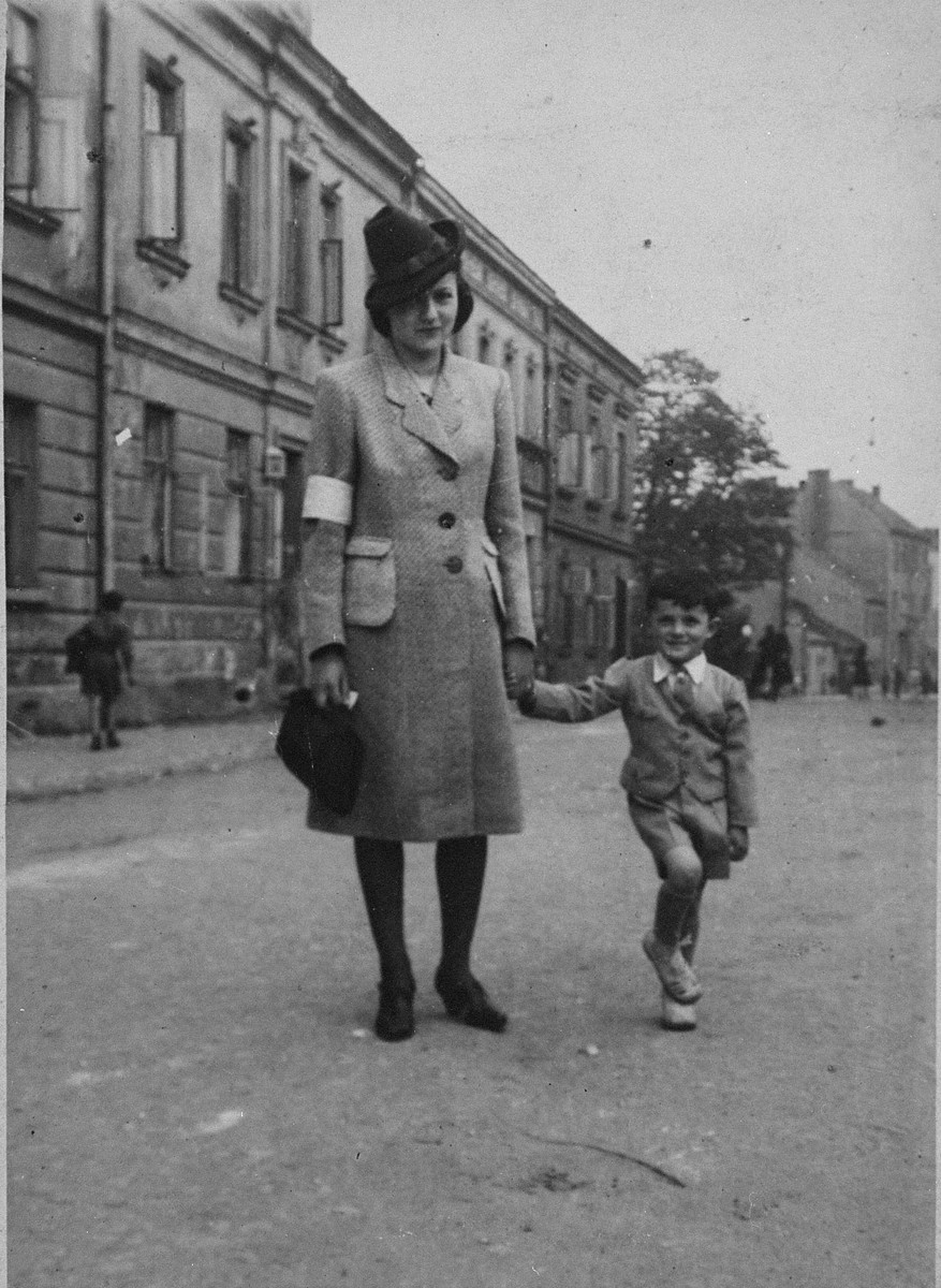 A Jewish mother, wearing an armband, walks along a street with her son in the Krakow ghetto.  Pictured are Nelly (Heffner) Finder, the cousin of donor Frieda Fisz, with her son, Fred.