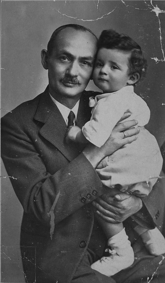 Studio portrait of a Jewish grandfather holding his grandson.  Pictured is Edward Heffner, holding his grandson Fred.  Edward in the uncle of donor Frieda Fisz.