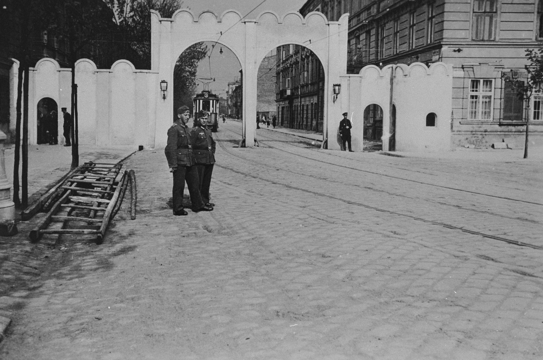 Two German soldiers pose near the gate at the entrance to the Krakow ghetto.