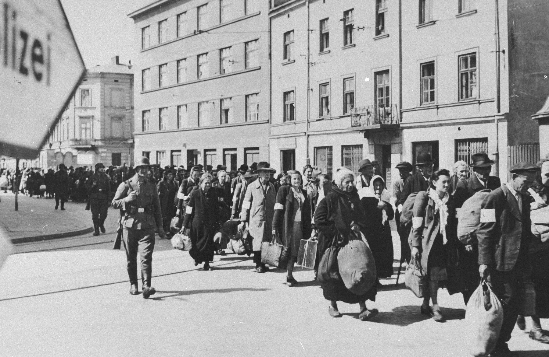 A column of Jews march with bundles down a main street in Krakow during the liquidation of the ghetto.  SS guards oversee the deportation action.