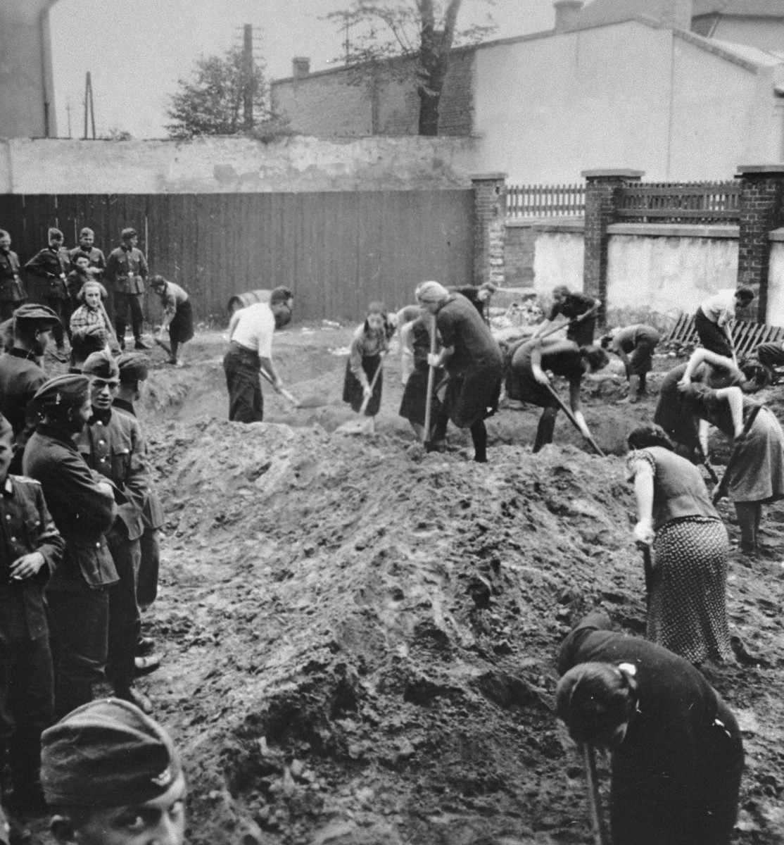 German troops look on as a group of Jews --all but one of whom are women-- dig ditches in a fenced-in lot in Krakow.