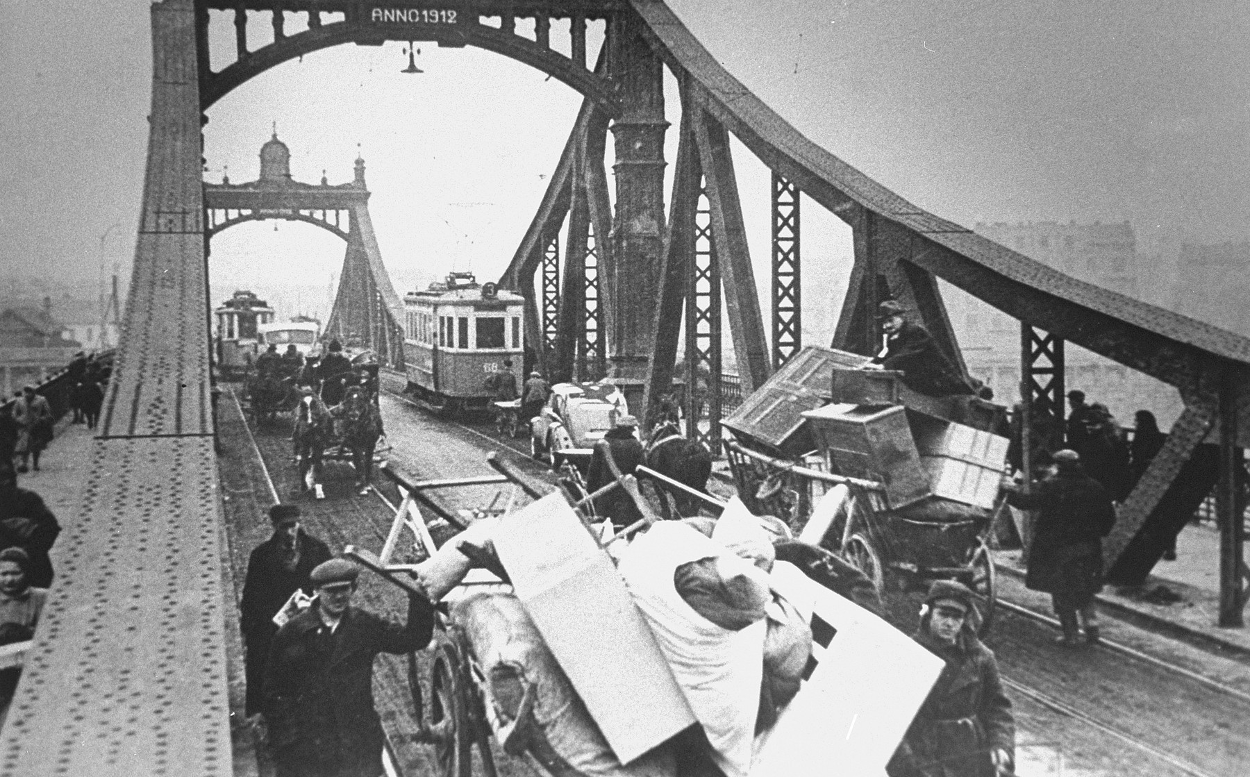 Jews who are being forced to relocate to the Krakow ghetto move their belongings in carts and horse-drawn wagons across the bridge over the Vistula River.