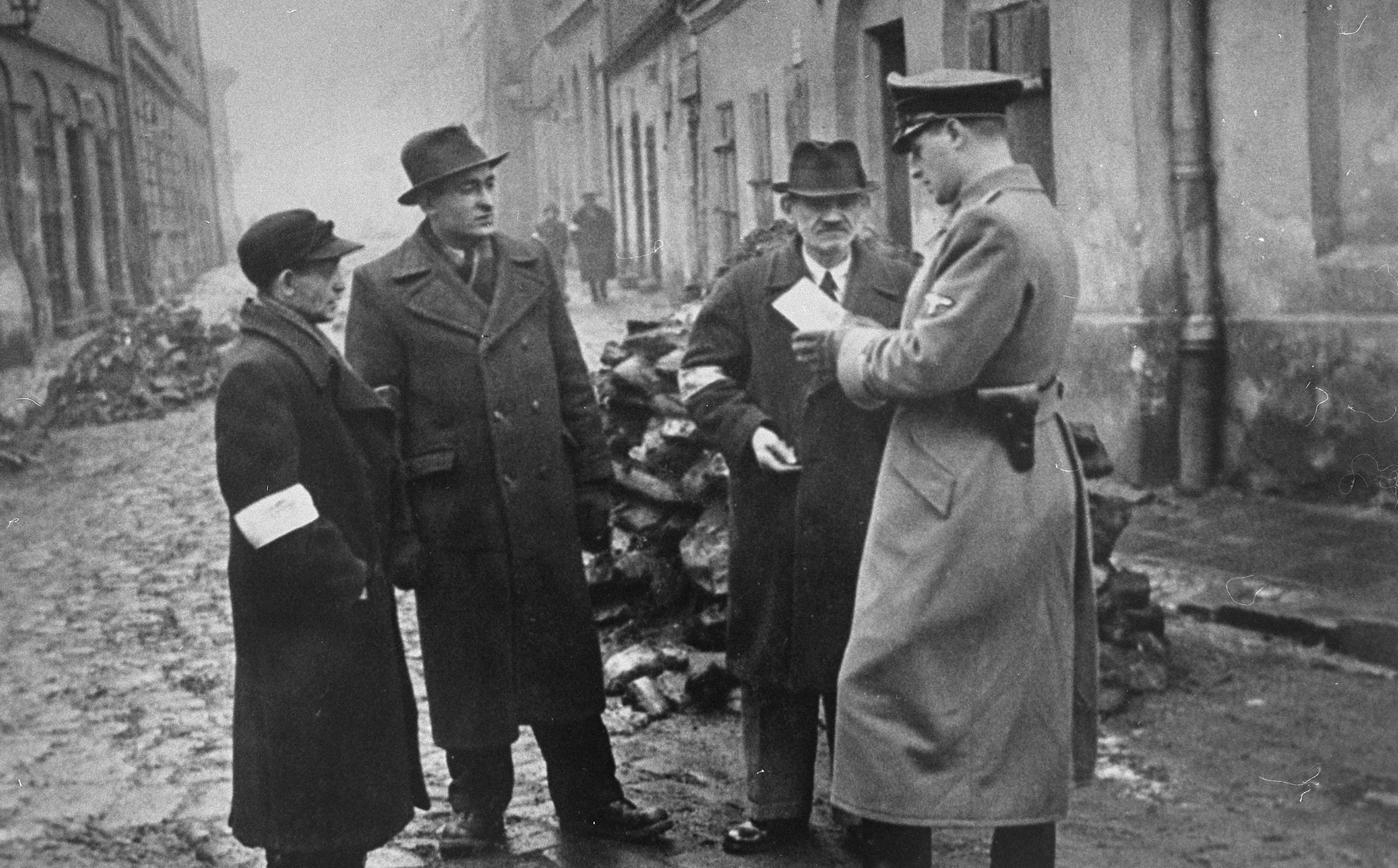 A German policeman checks the identification papers of Jews in the Krakow ghetto.