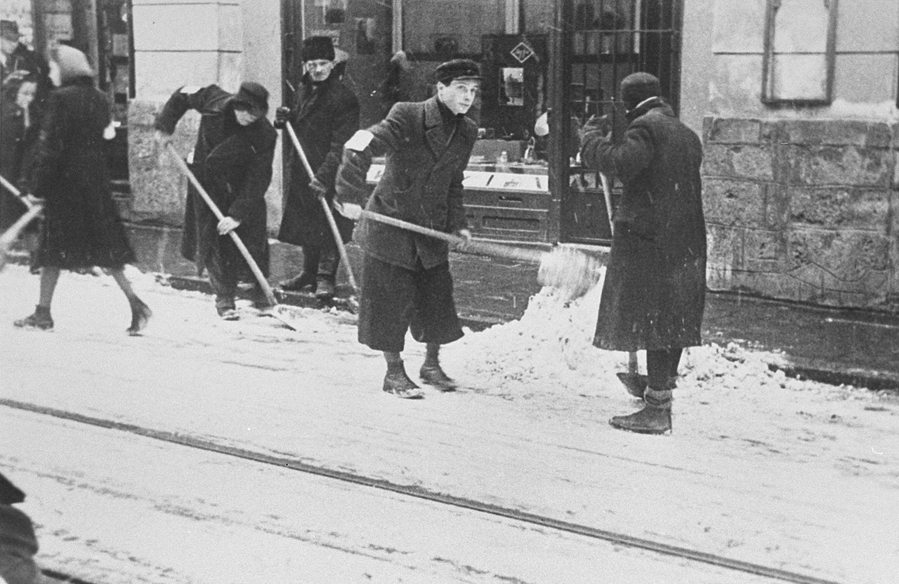 Jews wearing armbands are forced to shovel snow from the pavement in Krakow.