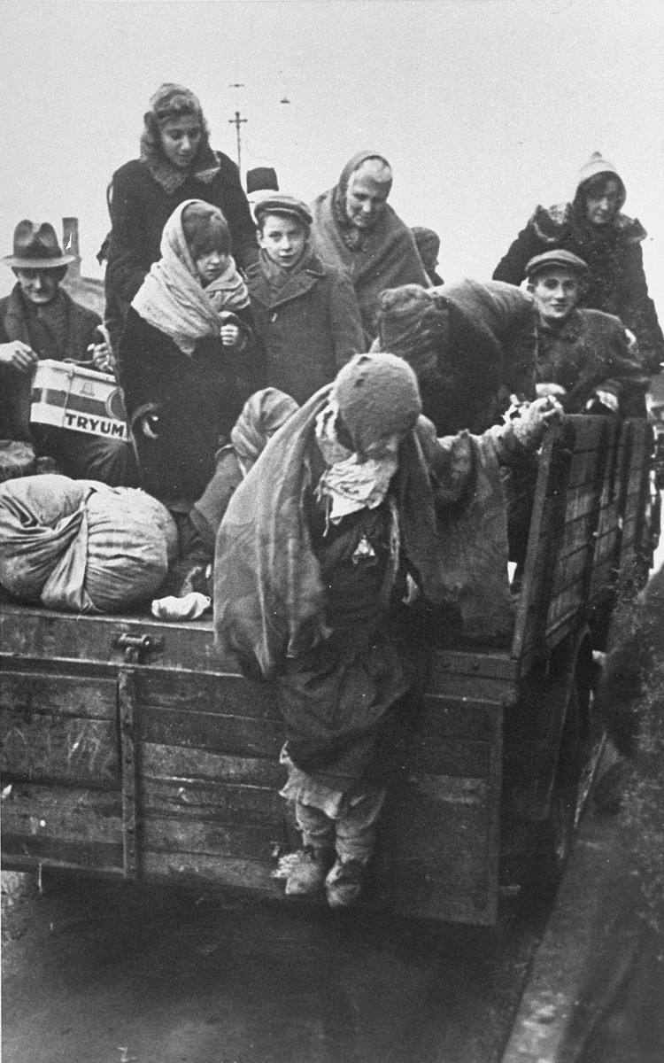 Jews from the Krakow ghetto, who have been rounded-up for deportation, are crowded onto the back of a truck.