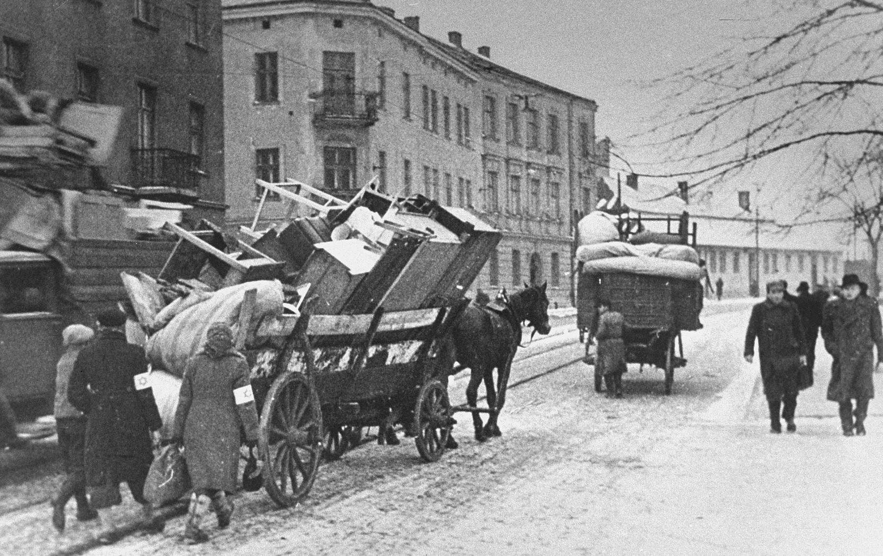Jews move their belongings into the Krakow ghetto in horse-drawn wagons.